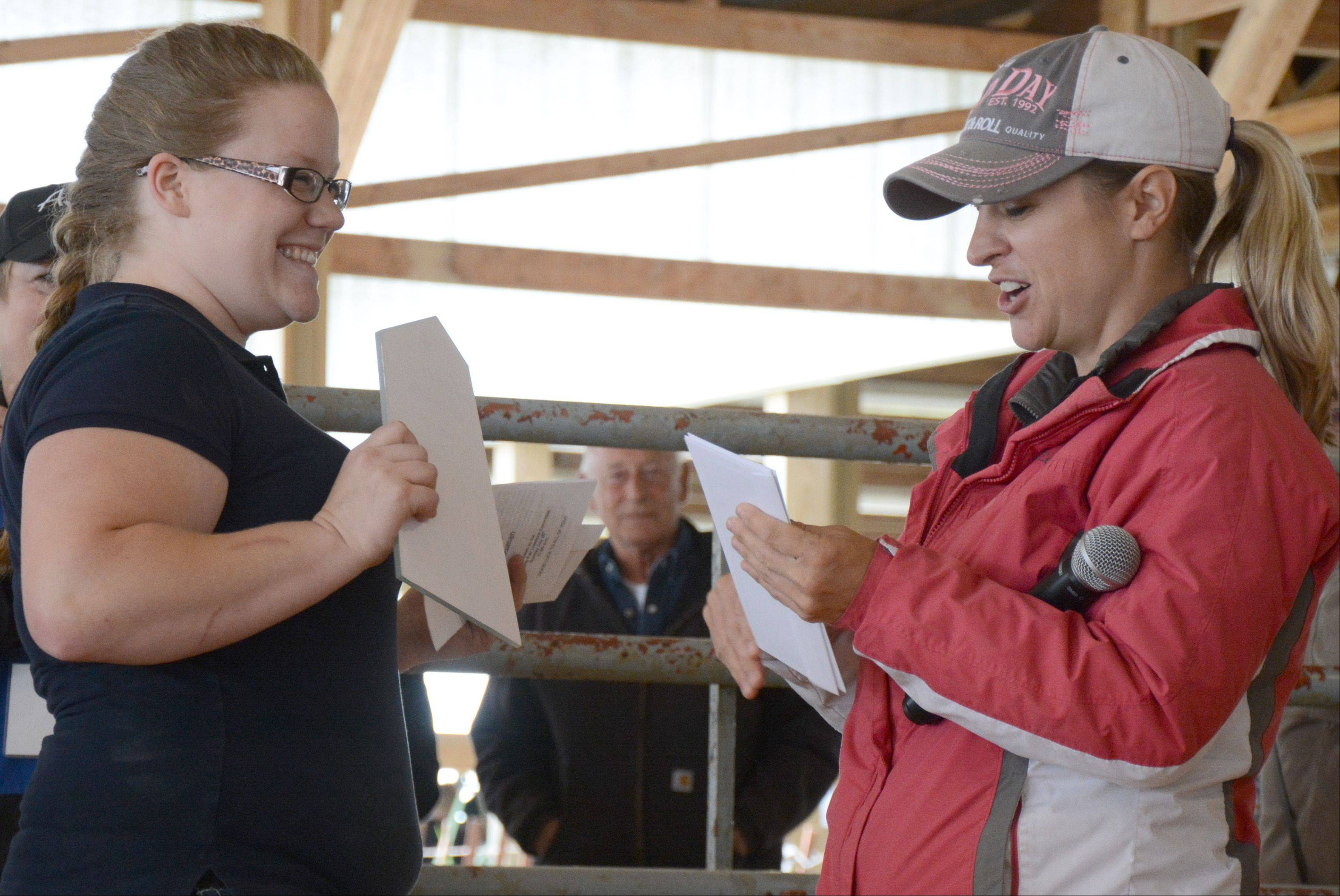 Shelby Grinnell, left, of Walworth, Wis., receives a plaque and a $300 check from Susie Fisher, of Zion, after winning first place in the Master Showman competition at the Lake County Fair Sunday.