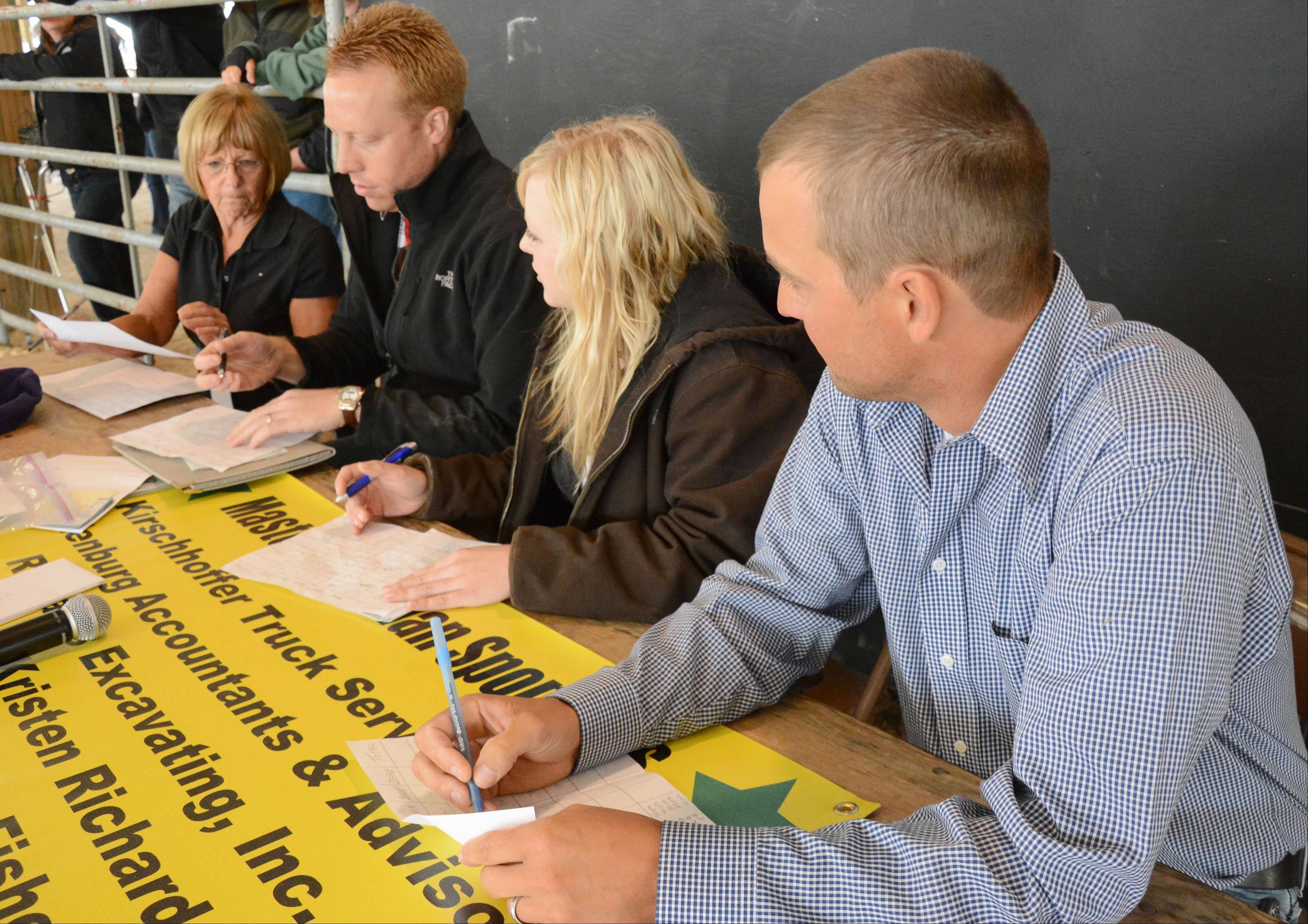 From right to left, judges Mike Richards, of Zion, Haley White, of Wauconda, Rick Doolittle, of Minneapolis, and Connie Davis, of Ingleside, tally the scores for the Master Showman competition Sunday at the Lake County Fair.