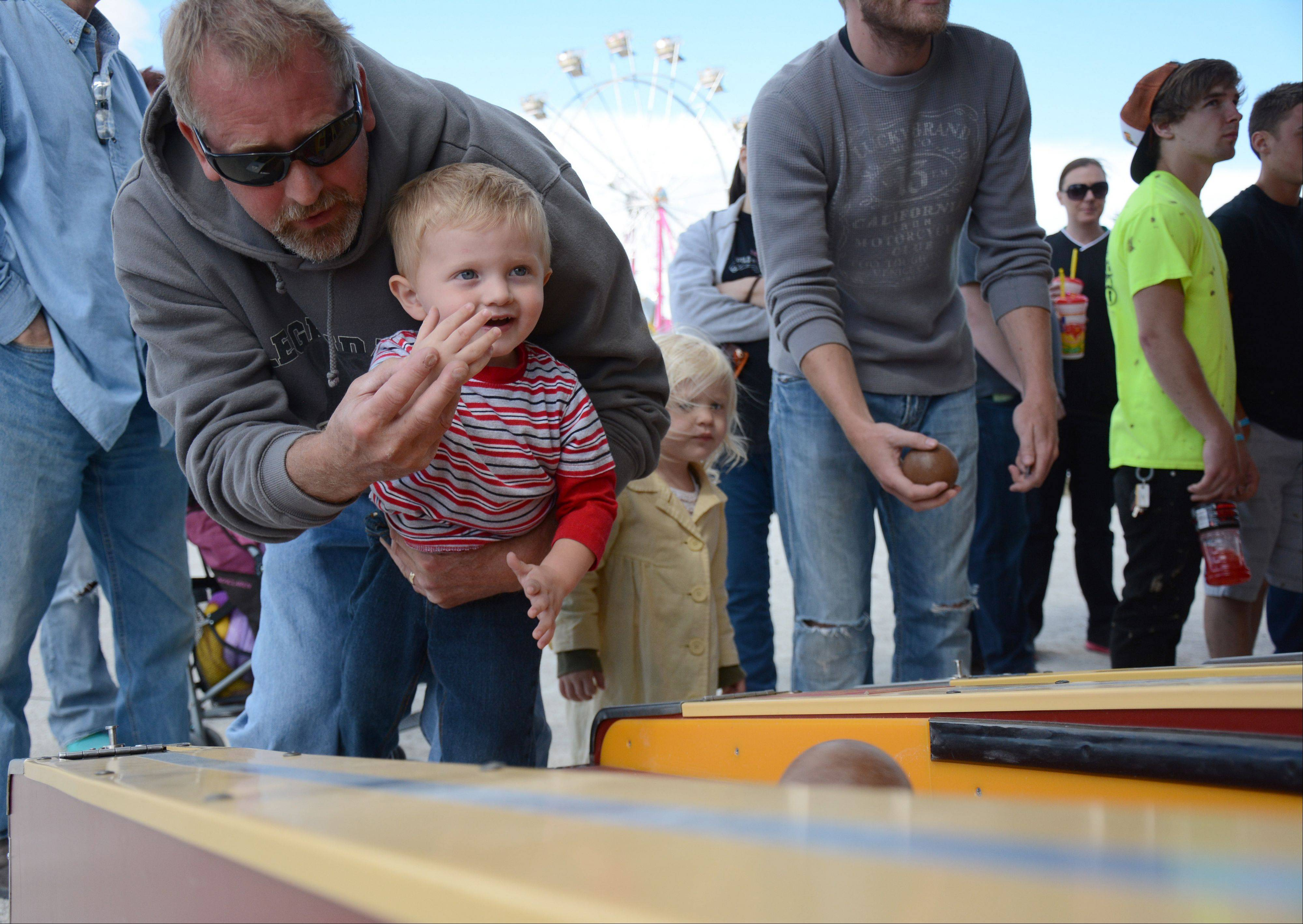Bill Joerger, of Mundelein, helps his grandson, Bill Jr. play Ski Ball at the Lake County Fair Sunday, July 28.