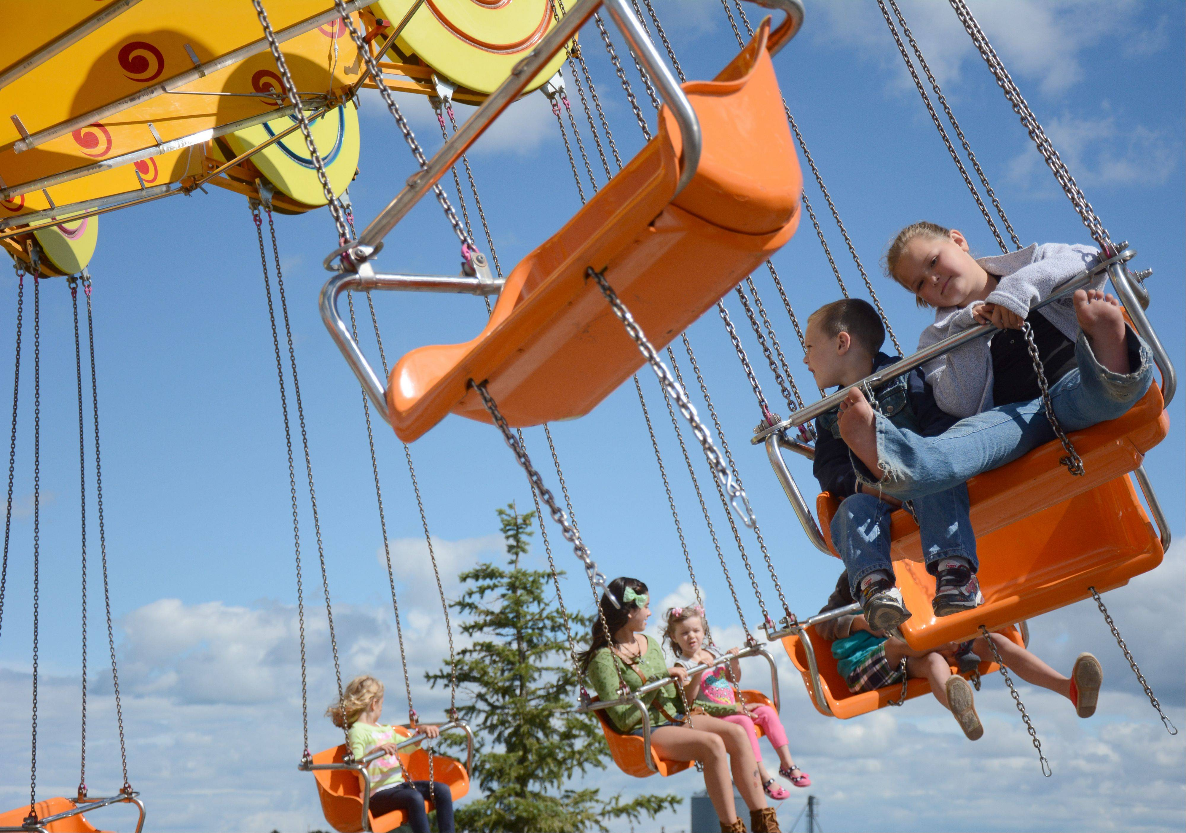 From left, Cullen Obrien, 3, and sister Aili, 9, both of Johnsburg, ride the Lolly Swing at the Lake County Fair Sunday, July 28.
