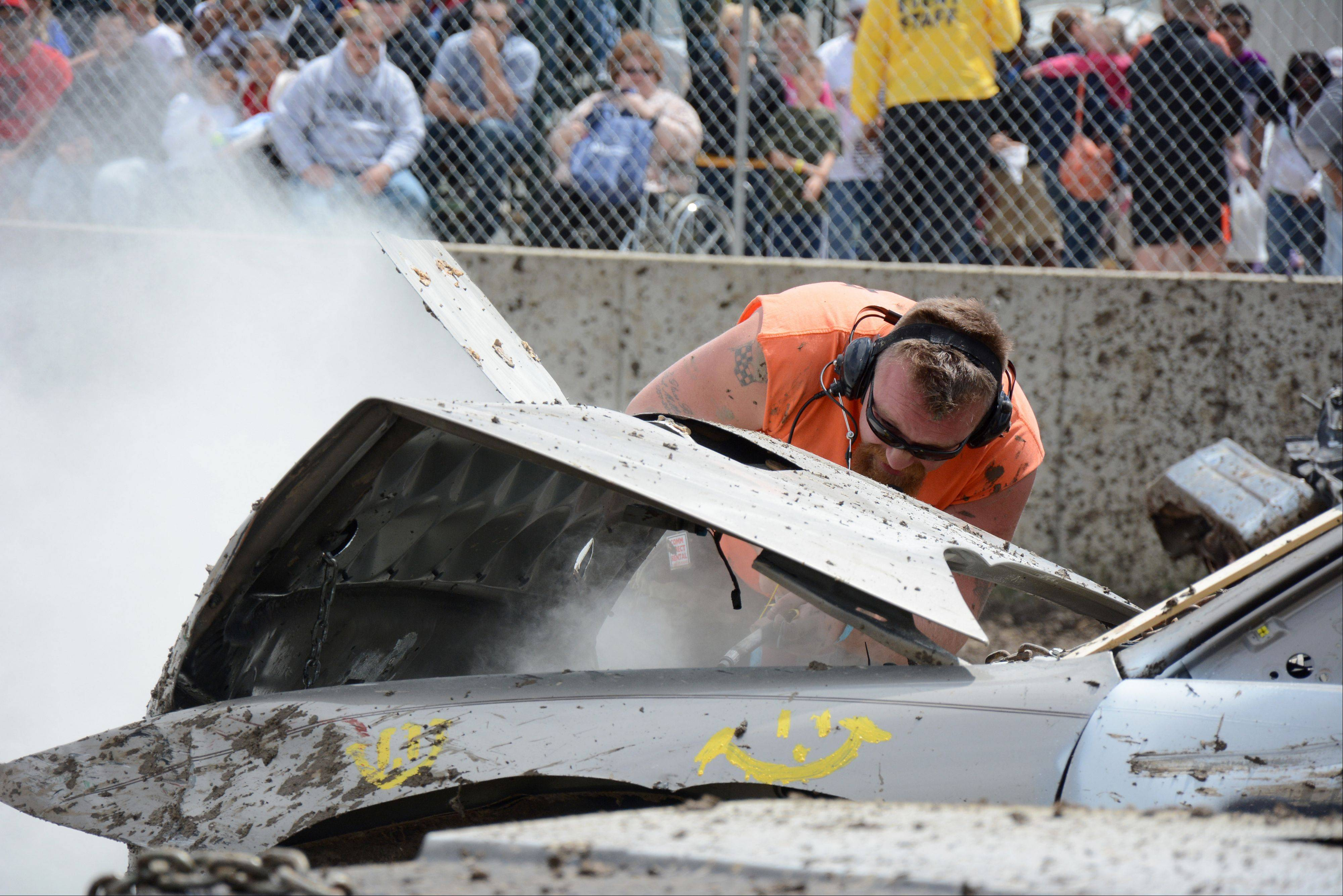 Paul Milbratz, of Wonder Lake, extinguishes a car fire during the Destruction Derby at the Lake County Fair Sunday, July 28.