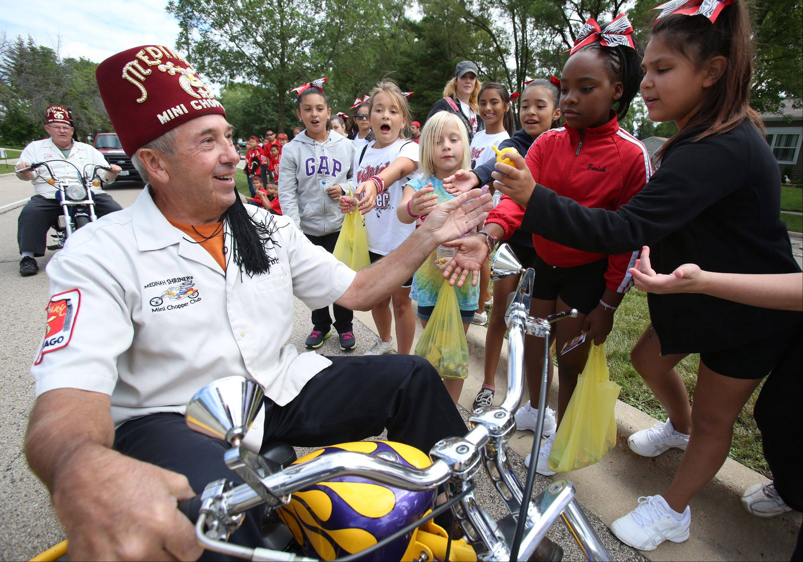 Scott Soldwisch with Medinah Shriners hands out small toy to children while riding a mini motorcycle in Streamwood Summer Celebration parade on Saturday.