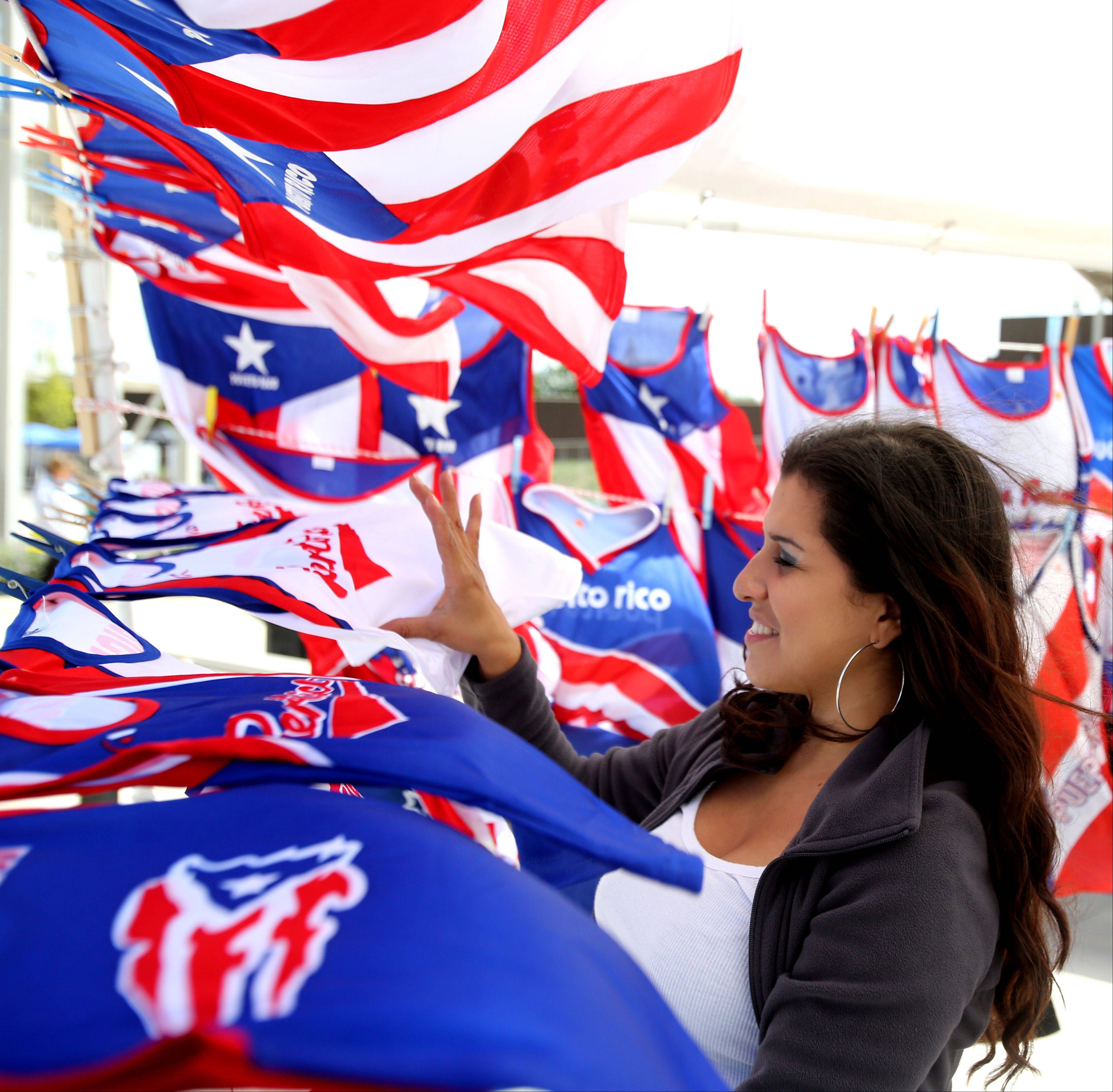 Vendor Yessica Guzman sells souvenir novelties during the Puerto Rican Heritage Fest at RiverEdge Park in Aurora.