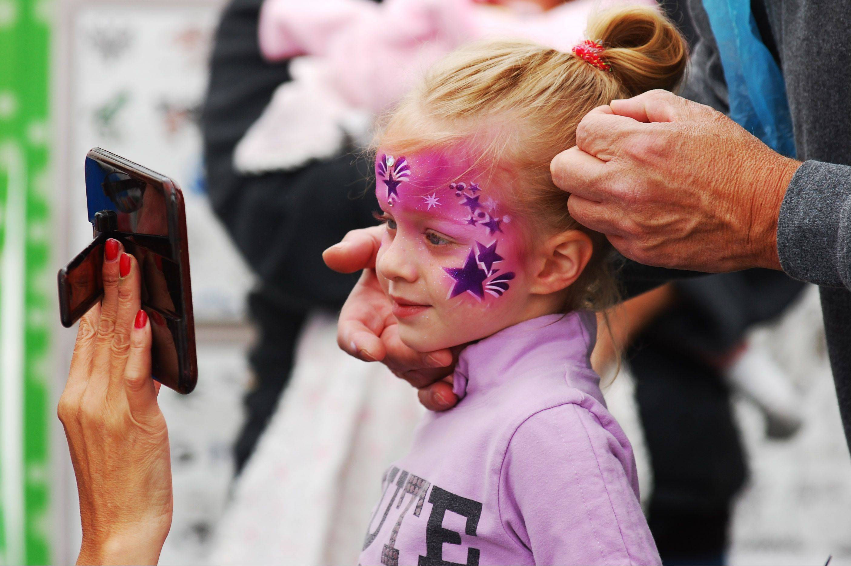 Peyton Jones, 4, of Big Rock gets a look at her start themed face paint at the Sugar Grove annual Corn Boil on Saturday, July 27. Grin and Wear It Face Painting was one of several activities at the Corn Boil.