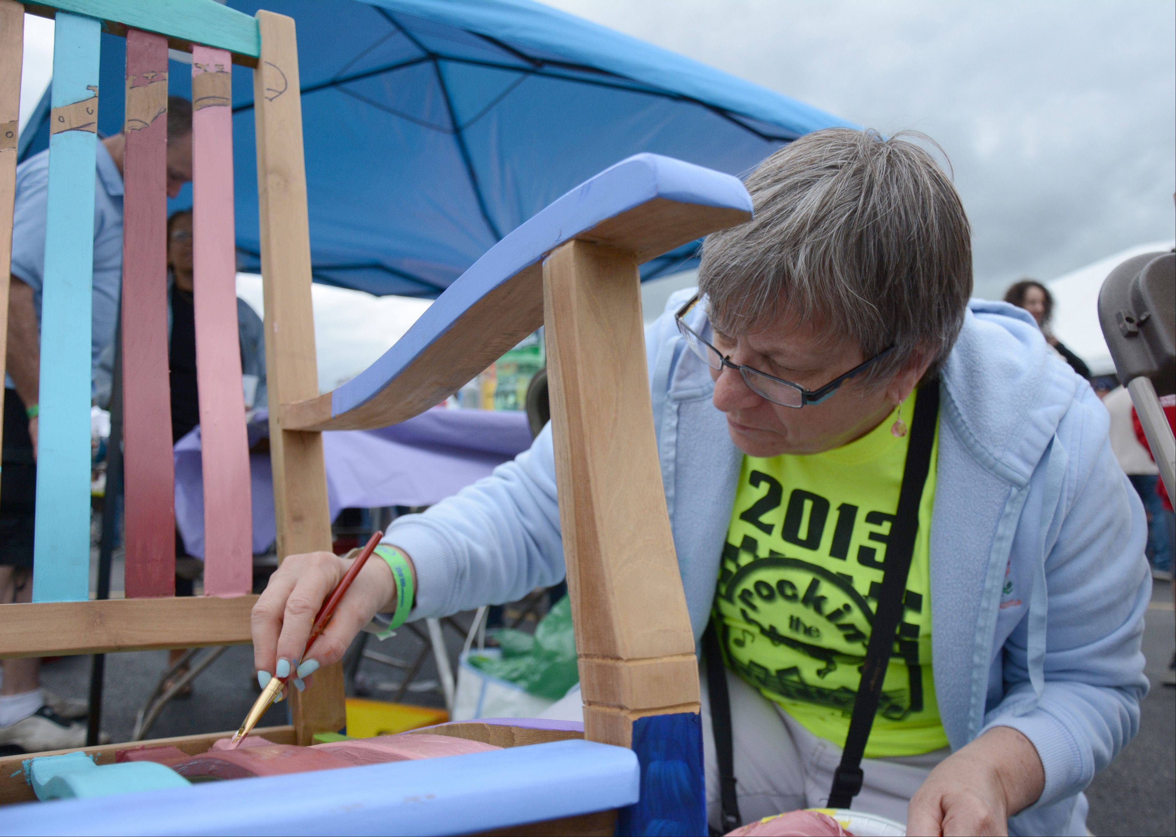 Kathy McLin, of Palatine, paints a rocking chair at the Rockin' the Blocks community block party in Palatine Saturday, July 27. The rocking chair will be donated to the Palatine Chamber of Commerce to be raffled off during the organizations movie night on August 18.
