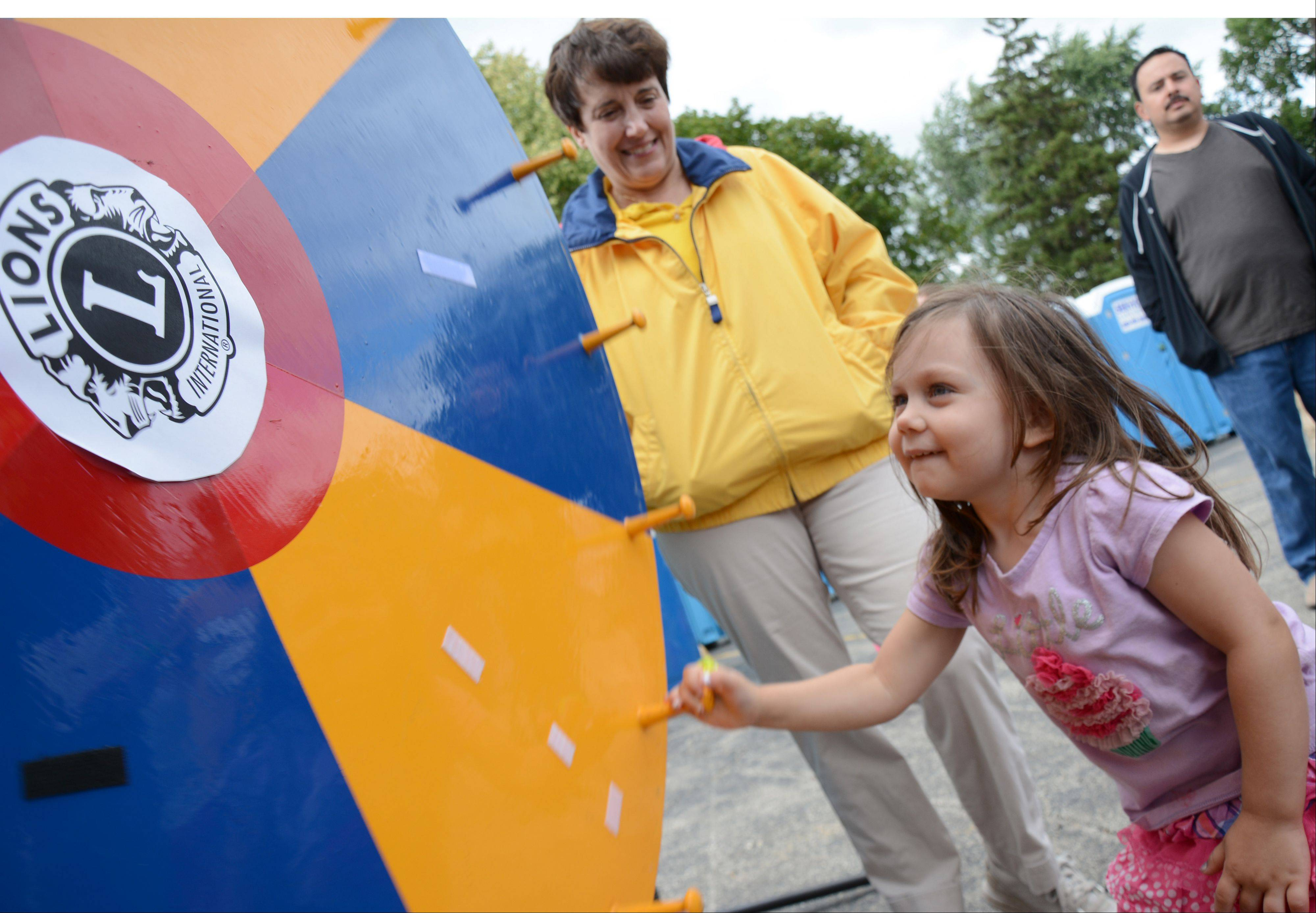 Ella Bain, 3, of Mount Prospect, spins a wheel to win a prize from the Mount Prospect Lions Club at the Mount Prospect Midsummer Downtown Block Party Saturday, July 27.