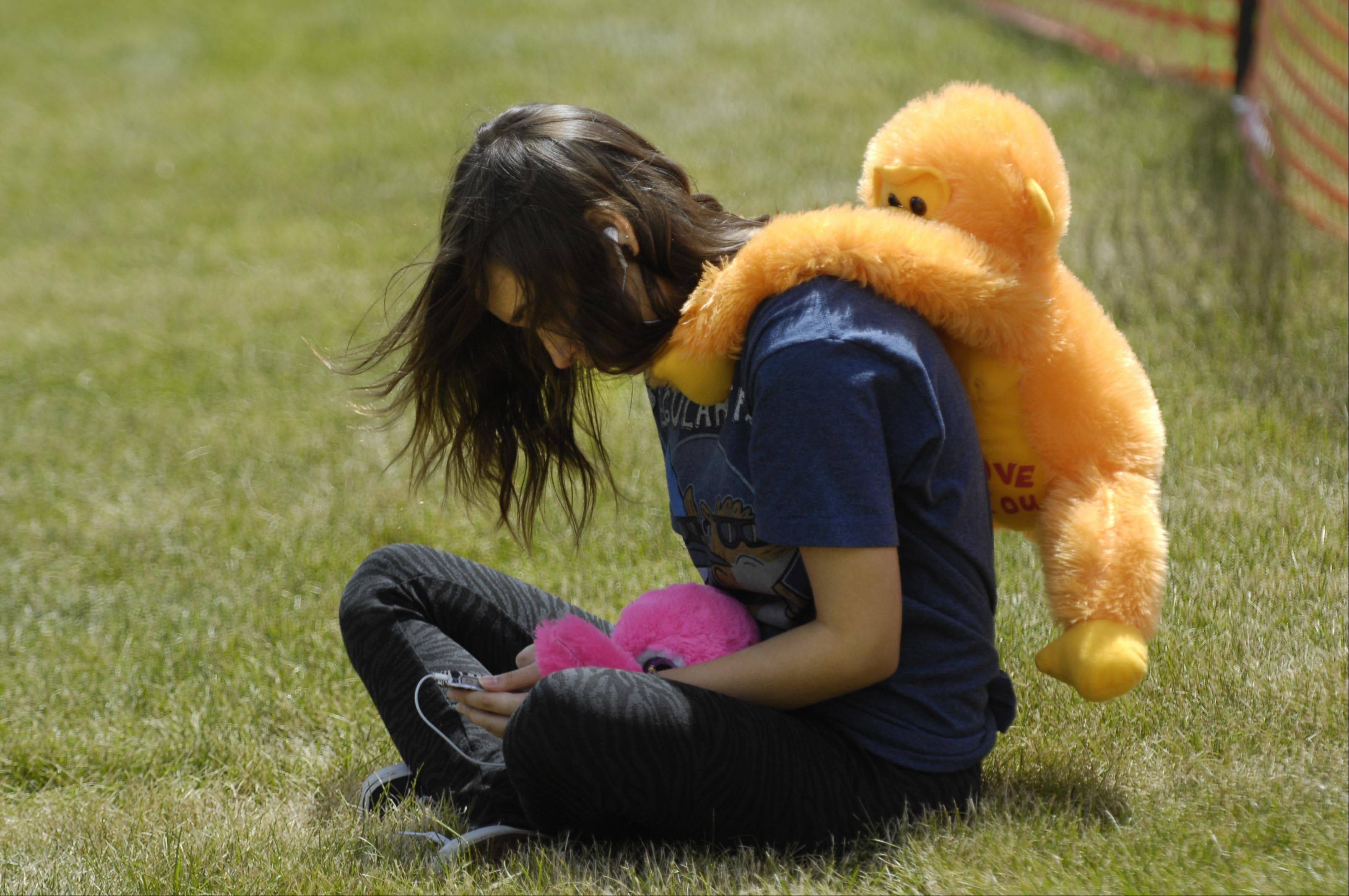 Ilma Skrgic, 16, waits with a monkey on her back for her younger sister, who was on the Yo-Yo ride at the final day of the Streamwood Summer Celebration in Hoover Grove Park on Irving Park Road Sunday.
