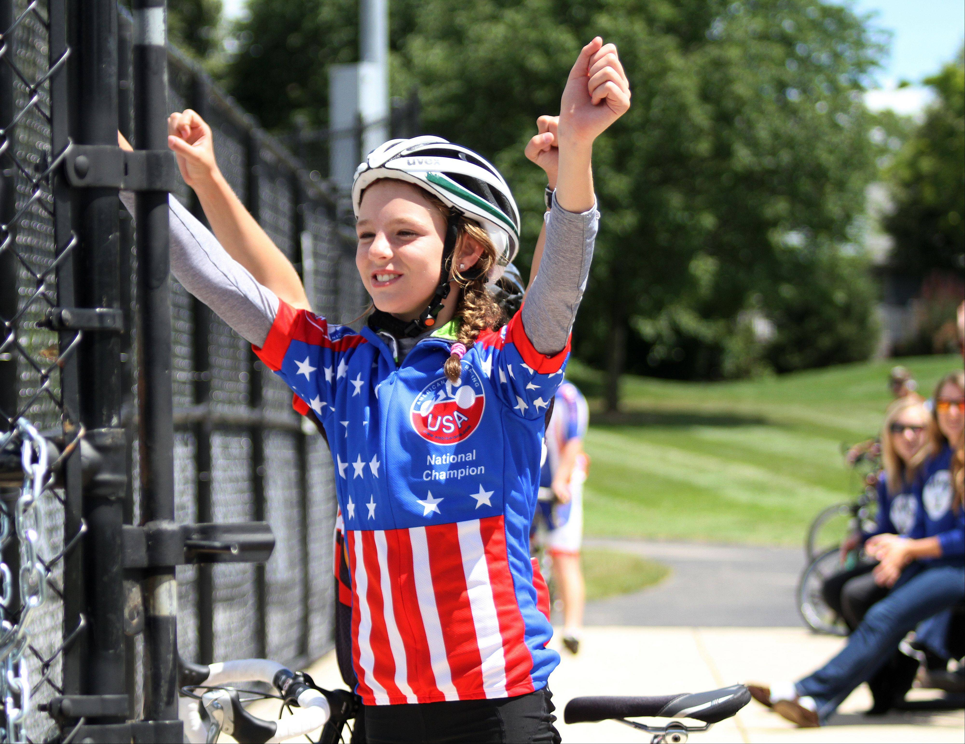 Danielle Krebs of St. Charles, 12, cheers on the BMX riders at the 2013 Winfield Criterium at Oakwood Park in Winfield on Sunday, July 28, 2013. Krebs won her race earlier in the day.