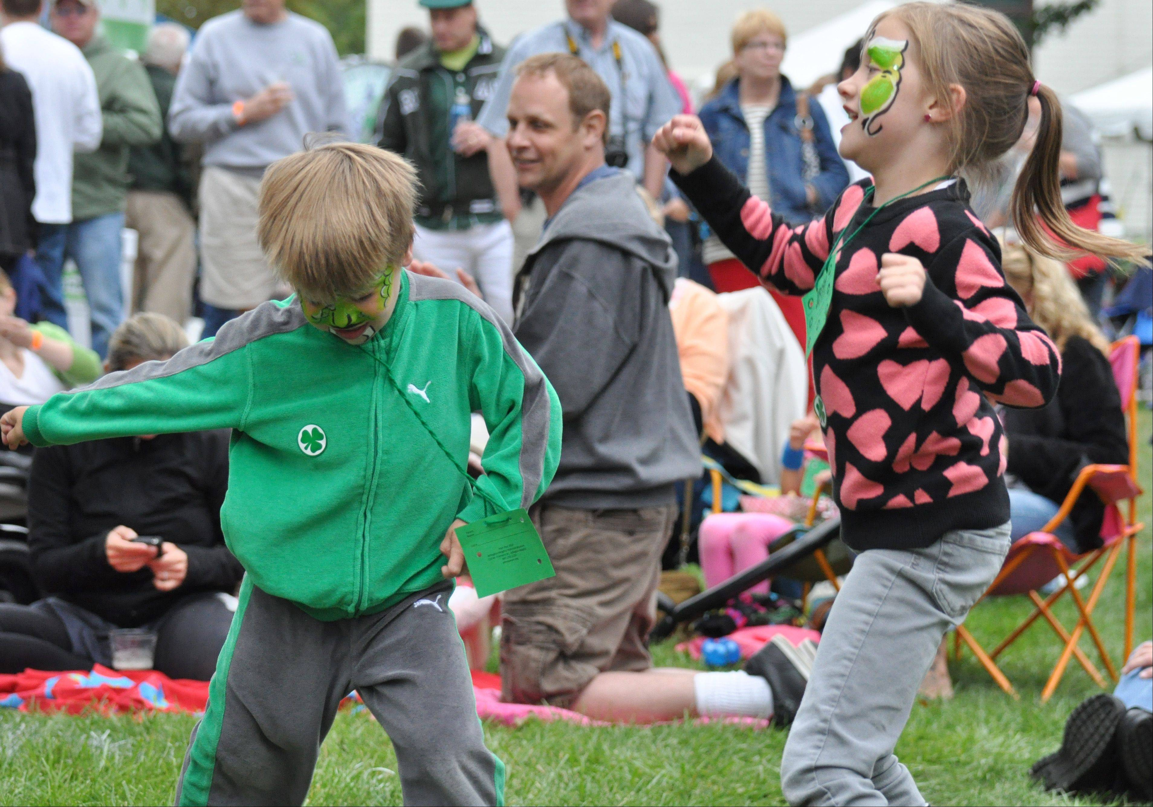 From left, Sam Frye, 5, and sister Isabel, 7, both of Arlington Heights dance to music at the Arlington Heights Irish Fest Saturday, July 27.