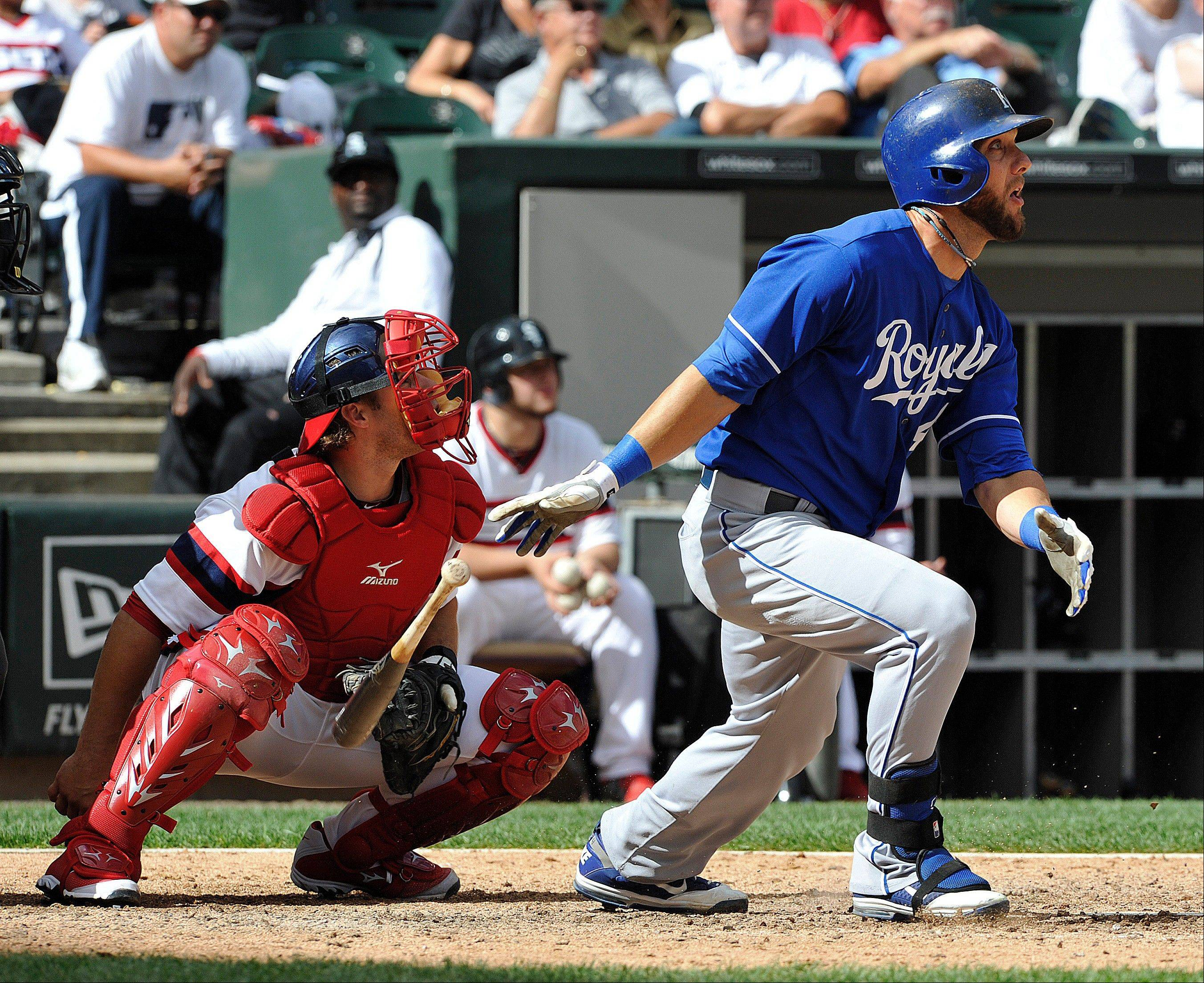 Tyler Flowers, left, looks on as Kansas City Royals' Alex Gordon hits a 2-run home against the Chicago White Sox during the 12th inning of a baseball game on Sunday, July 28, 2013, in Chicago.