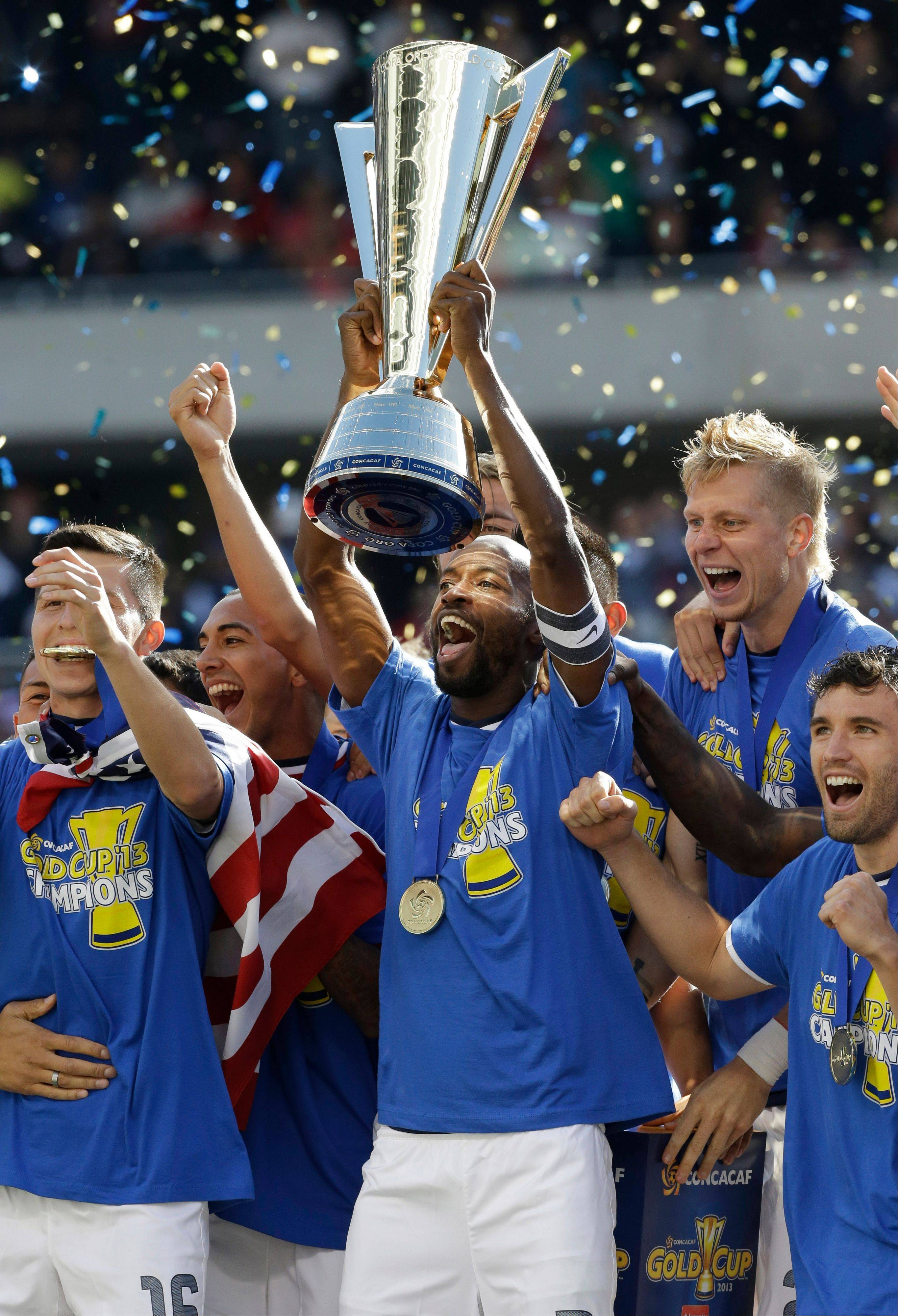United States defender DaMarcus Beasley (7), center, holds the trophy as he celebrates with teammates after defeating Panama 1-0 during the CONCACAF Gold Cup final soccer match at Soldier Field on Sunday.