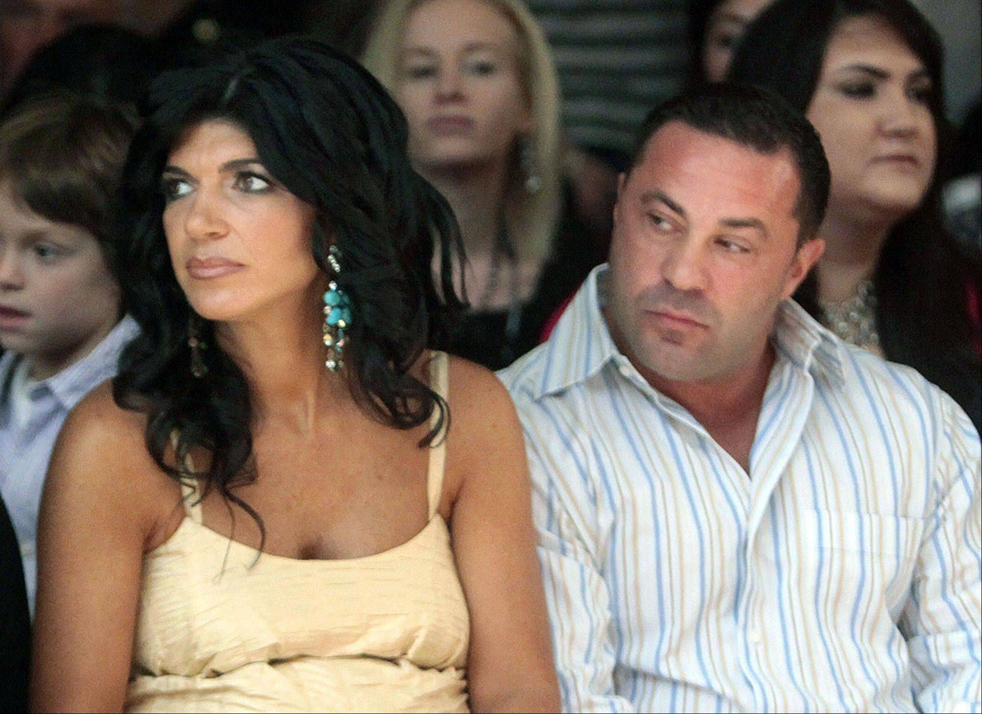 This Sept. 13, 2009 file photo originally released by Oral-B Pulsonic shows �Real Housewives of New Jersey� stars, Teresa Giudice, left, and her husband Joe Giudice at the Caravan Fashion Show sponsored by Oral-B Pulsonic in New York. Teresa and Giuseppe �Joe� Giudice were charged in a 39-count indictment handed up Monday in Newark, N.J. The two are accused of submitting fraudulent mortgage and other loan applications from 2001 through 2008, a year before their show debuted on Bravo. Prosecutors say they made false claims about their employment status and salaries.
