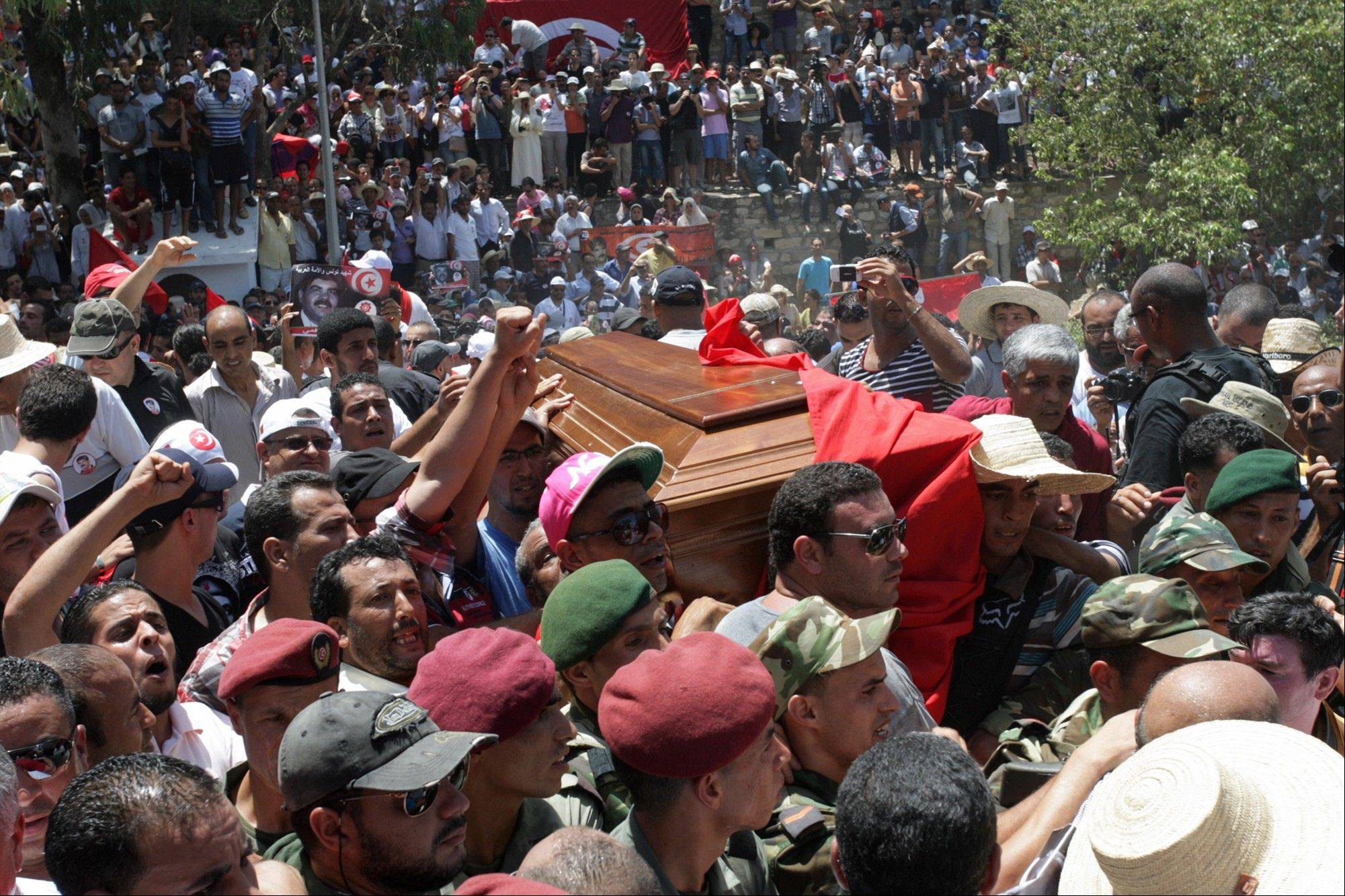 Tunisians carry the coffin of Tunisian opposition politician Mohammed Brahmi during his funeral at Jallez Cemetery in Tunis, Saturday July, 27, 2013. Mohamed Brahmi was shot 14 times in front of his home within sight of his family on Thursday, plunging the country into a political crisis and unleashing demonstrations around the country blaming the government for the assassination. Tunisia�s prime minister said Monday the government will not step down despite opposition demands.