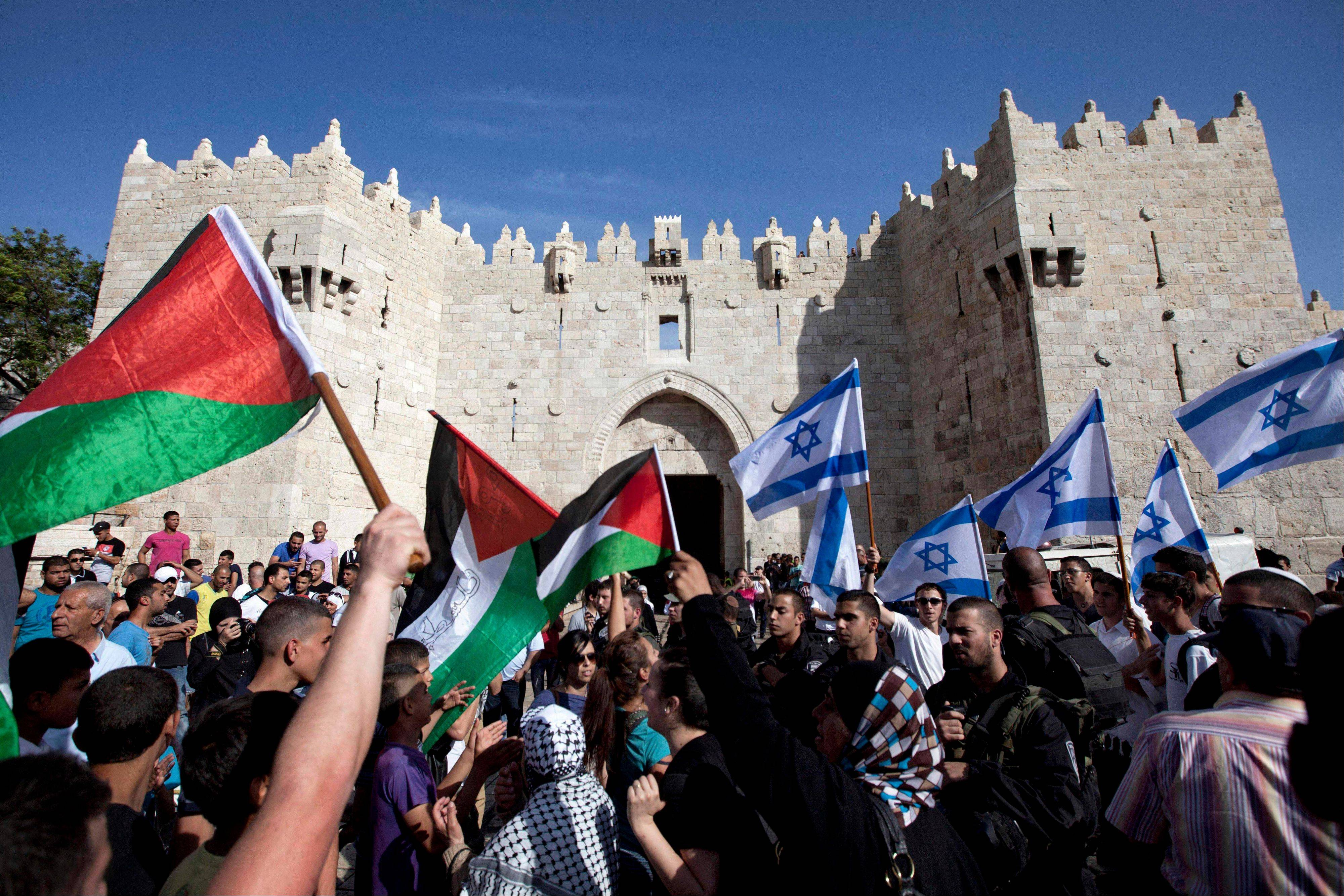 Israelis and Palestinians wave flags as Israelis march celebrating Jerusalem Day outside Damascus Gate in Jerusalem's old city on May 8. The U.S. on Sunday announced the resumption of Israeli-Palestinian talks following years of stalemate, after Israel's Cabinet agreed to release 104 Palestinian prisoners convicted of deadly attacks. The return to direct contacts between the sides gave U.S. Secretary of State John Kerry his first concrete achievement after months of shuttle diplomacy.
