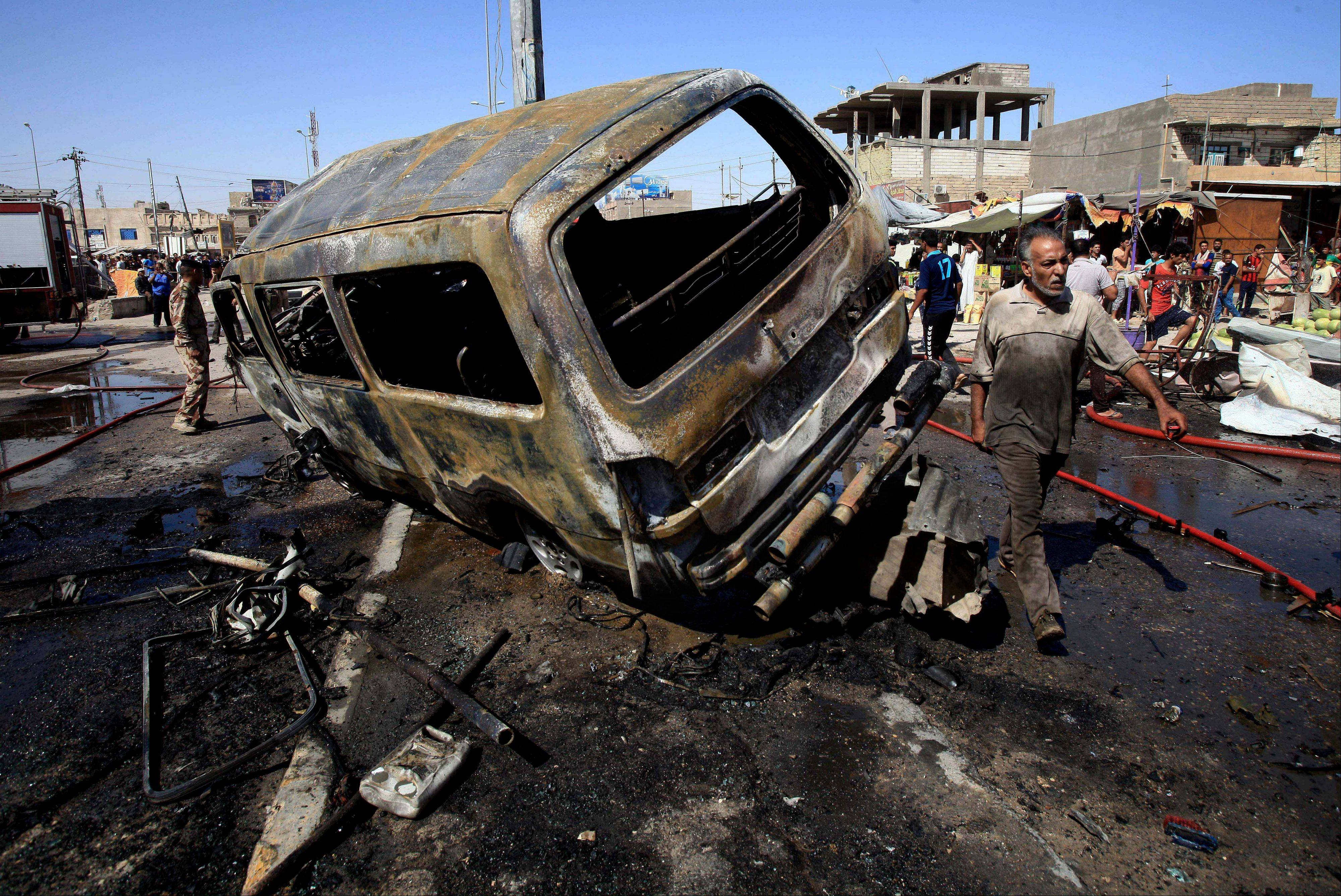 People and security forces inspect the site of a car bomb explosion in Basra, 340 miles southeast of Baghdad, Iraq, Monday. A wave of over a dozen car bombings hit central and southern Iraq during morning rush hour on Monday, officials said, killing scores in the latest coordinated attack by insurgents determined to undermine the government.