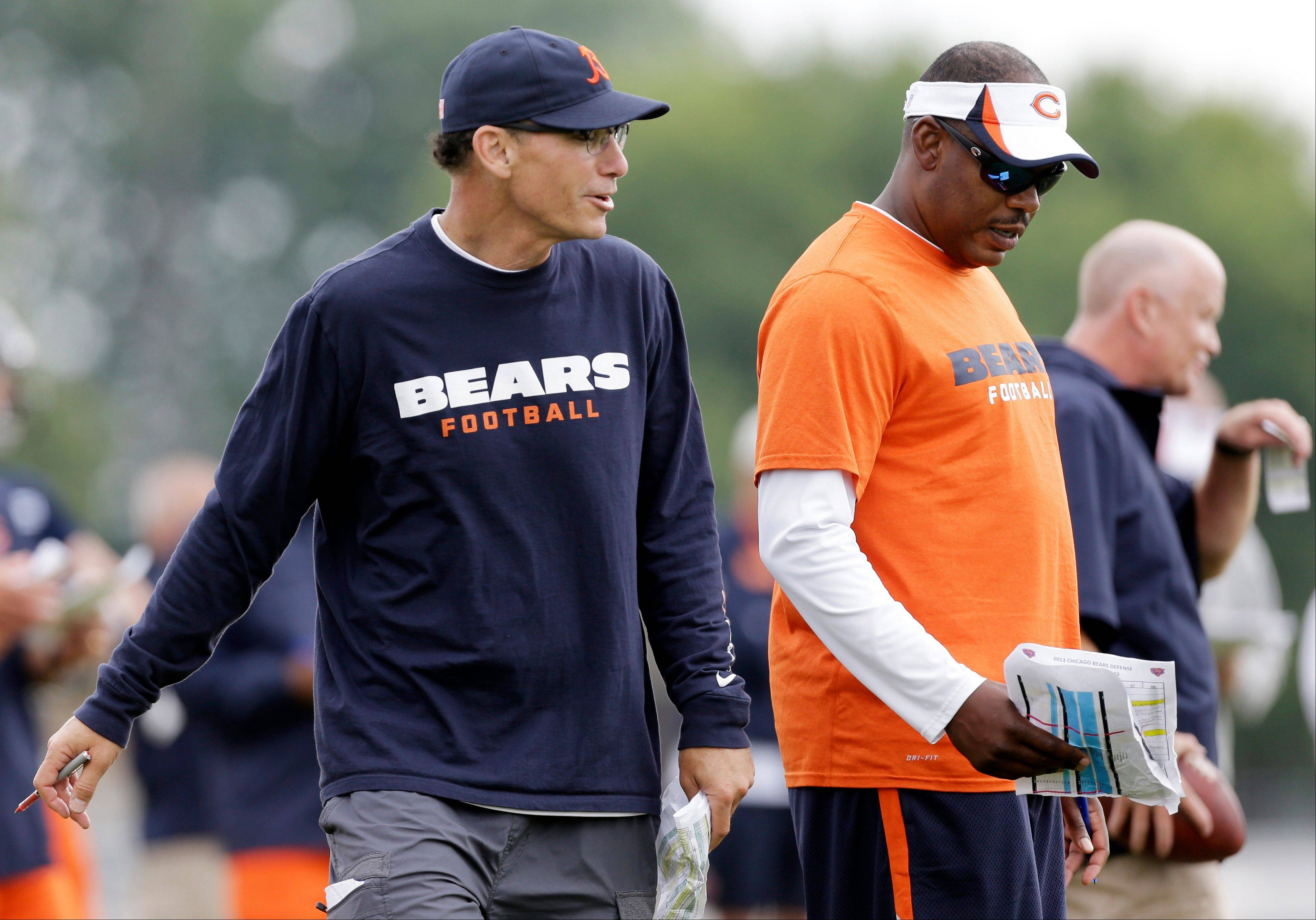 Bears head coach Marc Trestman, left, chats with defensive coordinator Mel Tucker during training camp.