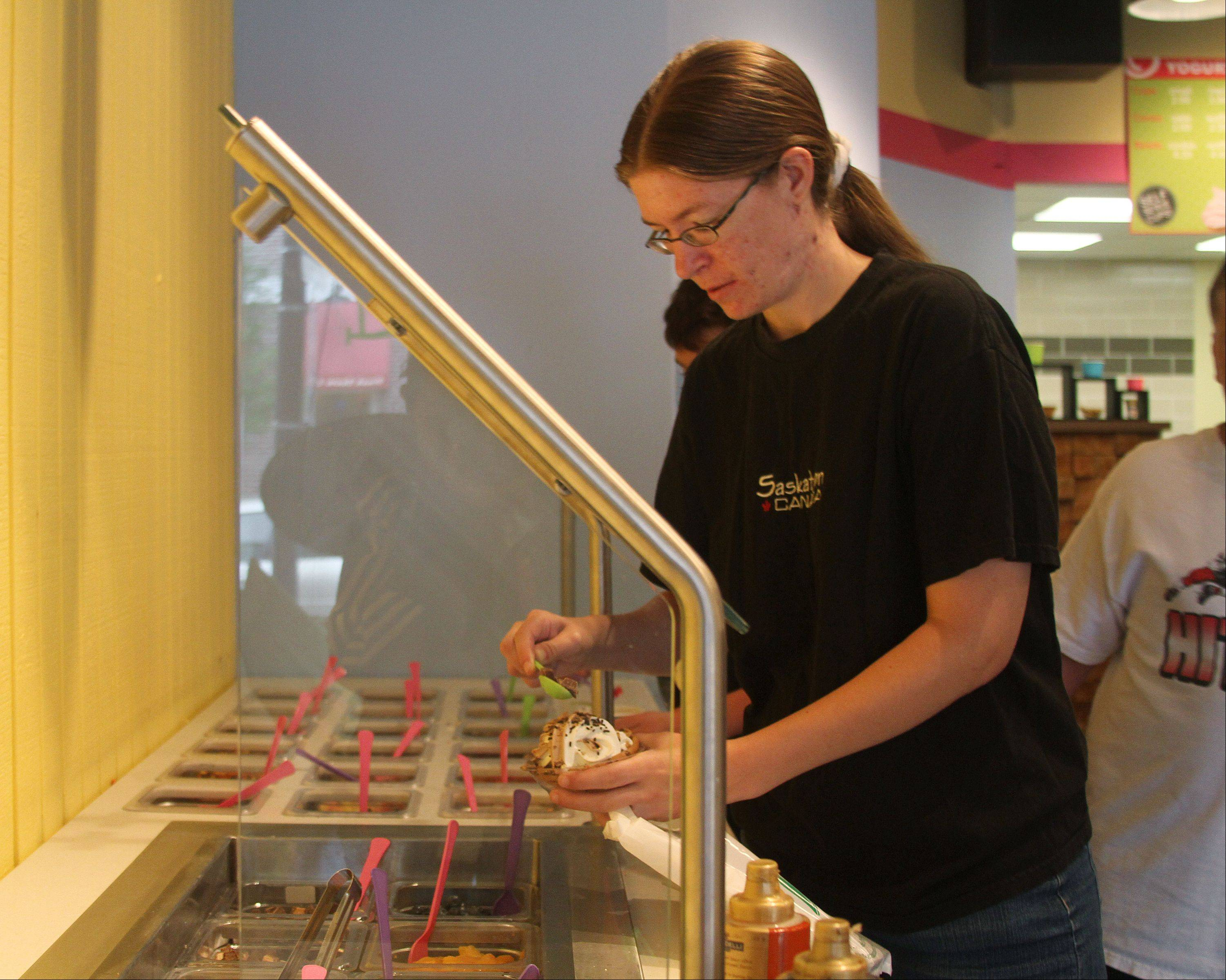 Kelly Mueller of Naperville tops her chocolate and vanilla swill frozen yogurt at the new B Happy Cafe at 206 S. Washington St. in downtown Naperville. The cafe opened July 13 featuring self-serve frozen yogurt in three sizes without a scale for pricing based on weight.