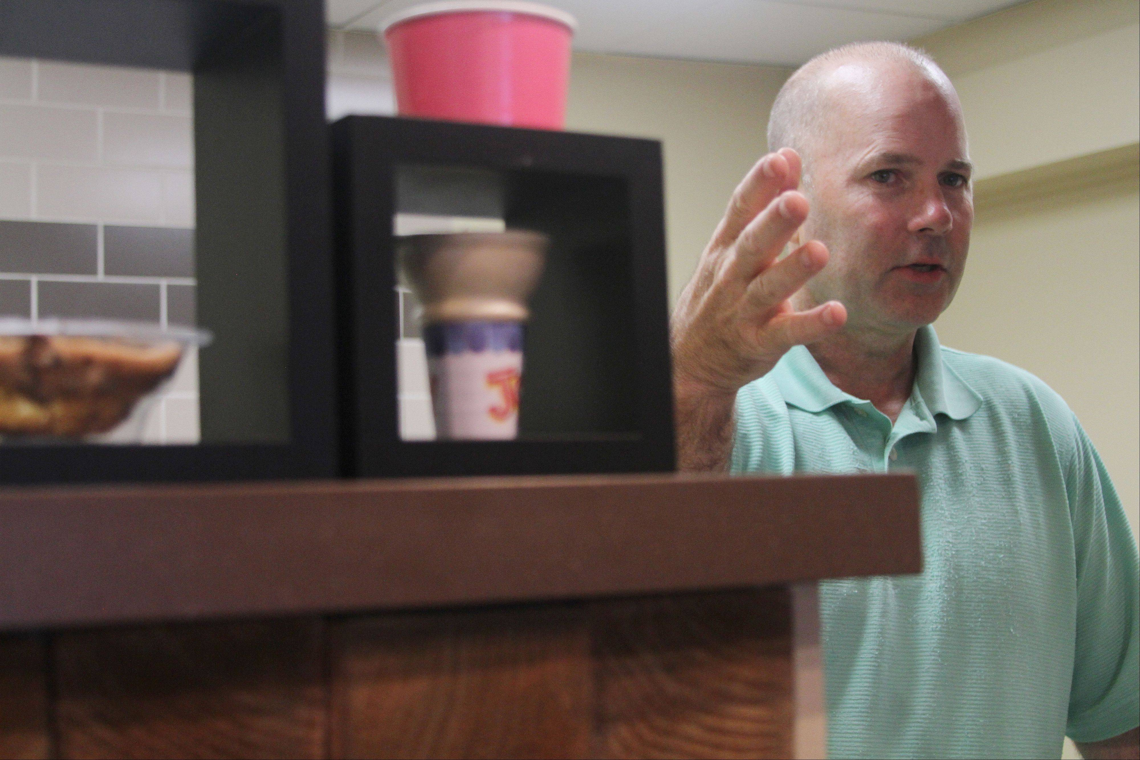 Michael Prince, owner of B Happy Cafe at 206 S. Washington St. in downtown Naperville, explains the process of his self-serve frozen yogurt shop to new customers. Unlike other frozen yogurt shops that weigh the cups, B Happy Cafe has a set price for each size.