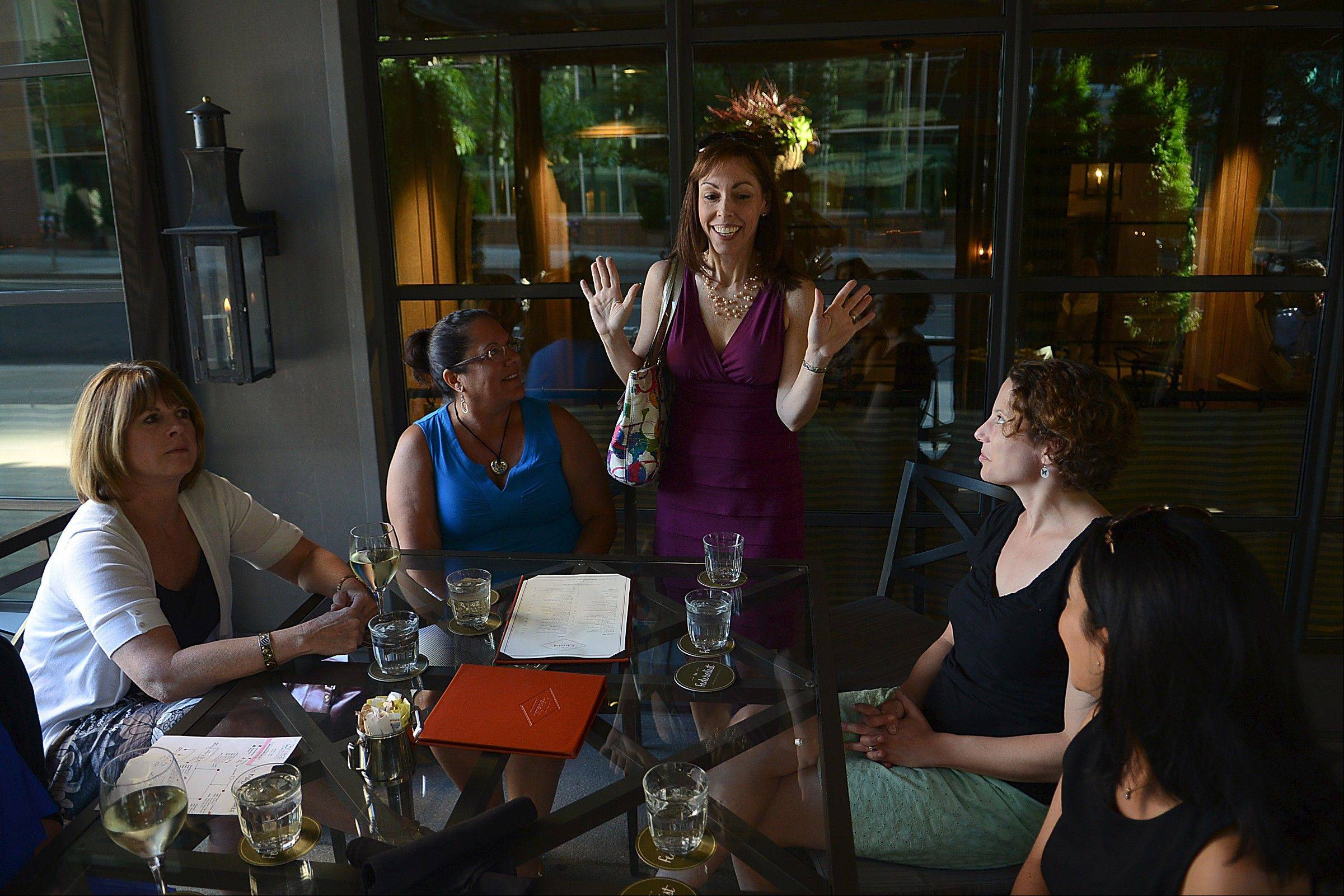 Lisa Schlager, standing, greets other women who are genetically predisposed to develop cancer. The get-together was organized so attendees could share stories of diagnoses and treatments.