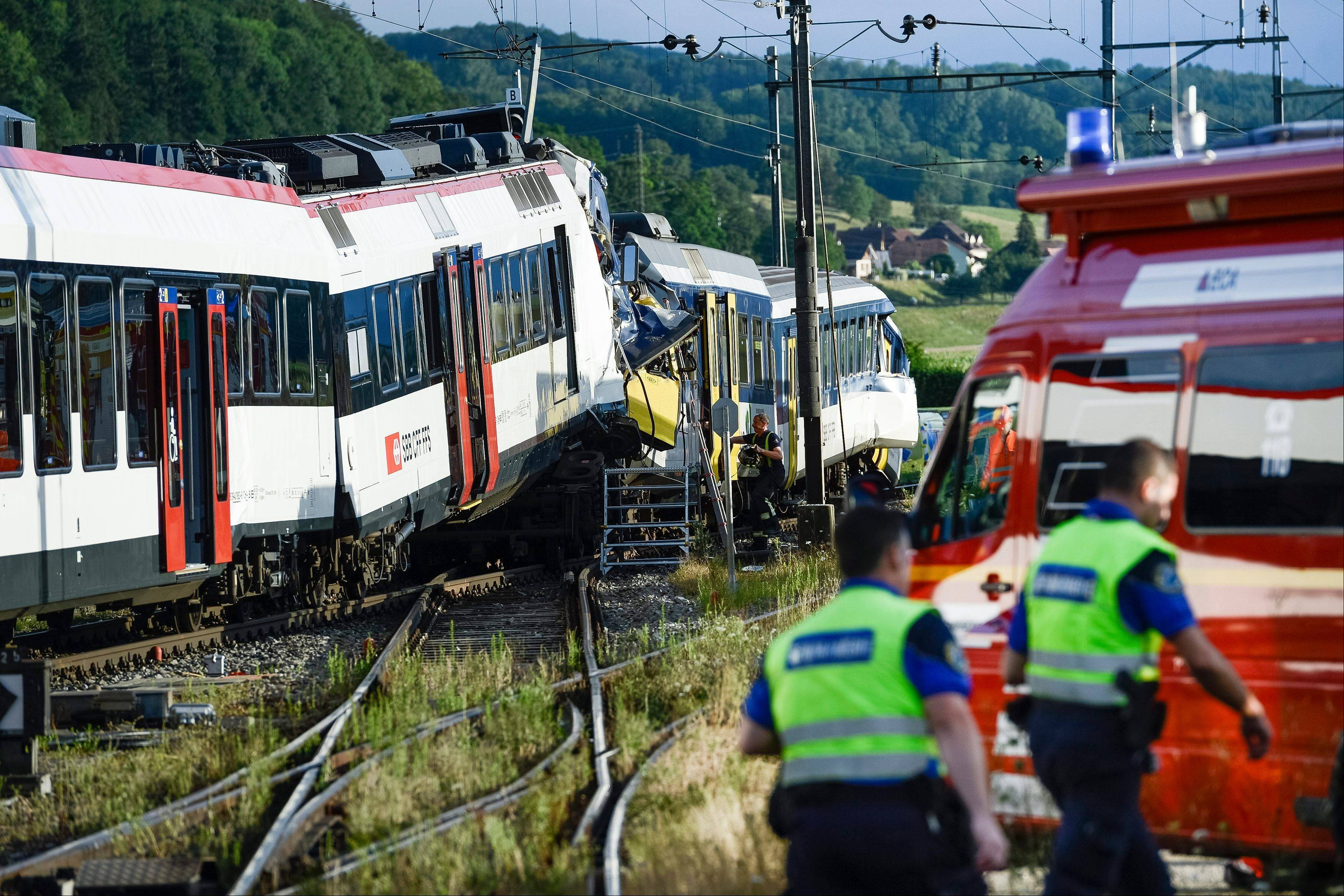 Rescue personnel work at the site where two passenger trains collided head-on in Granges-pres-Marnand, western Switzerland, Monday, July 29, 2013. Numerous people have been injured.
