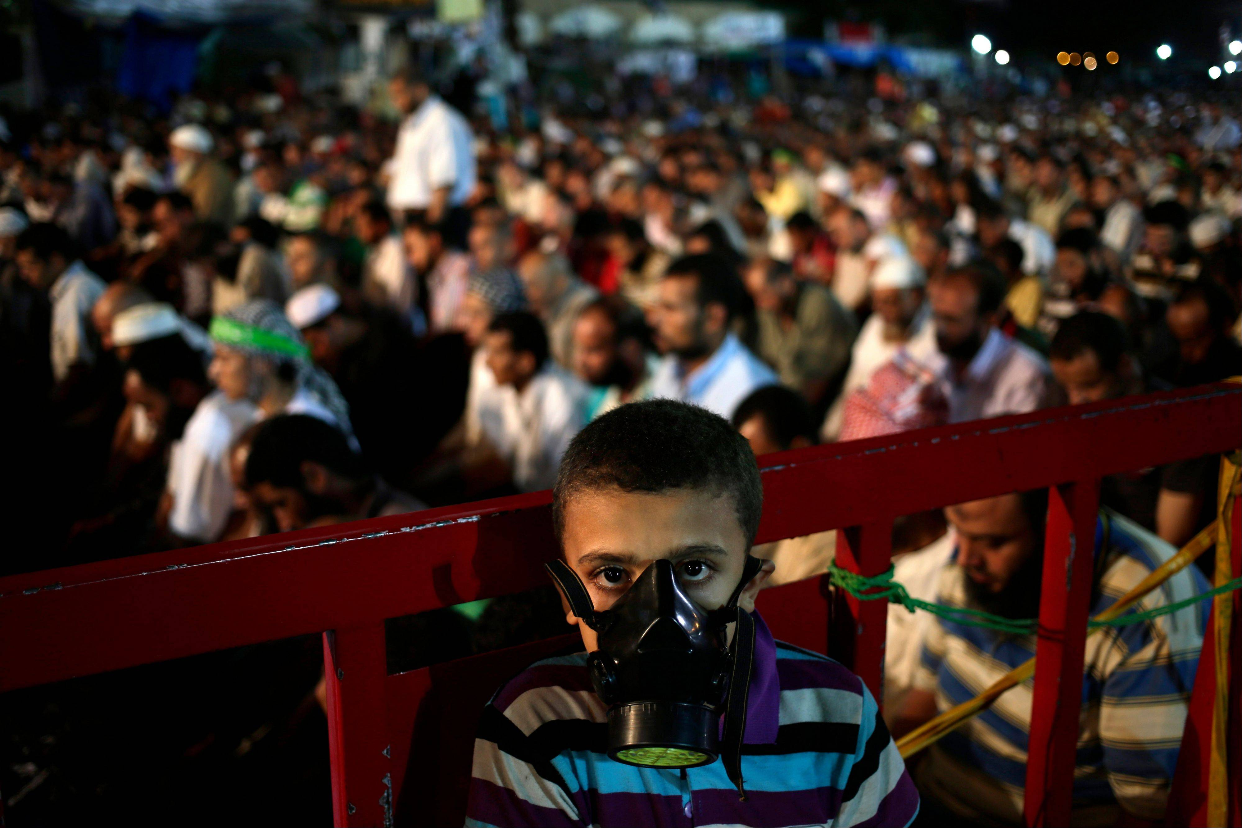 A boy wears a tear gas mask as supporters of Egypt's ousted President Mohammed Morsi pray at Nasr City, where protesters have installed a camp and hold daily rallies, in Cairo, Egypt, Sunday.