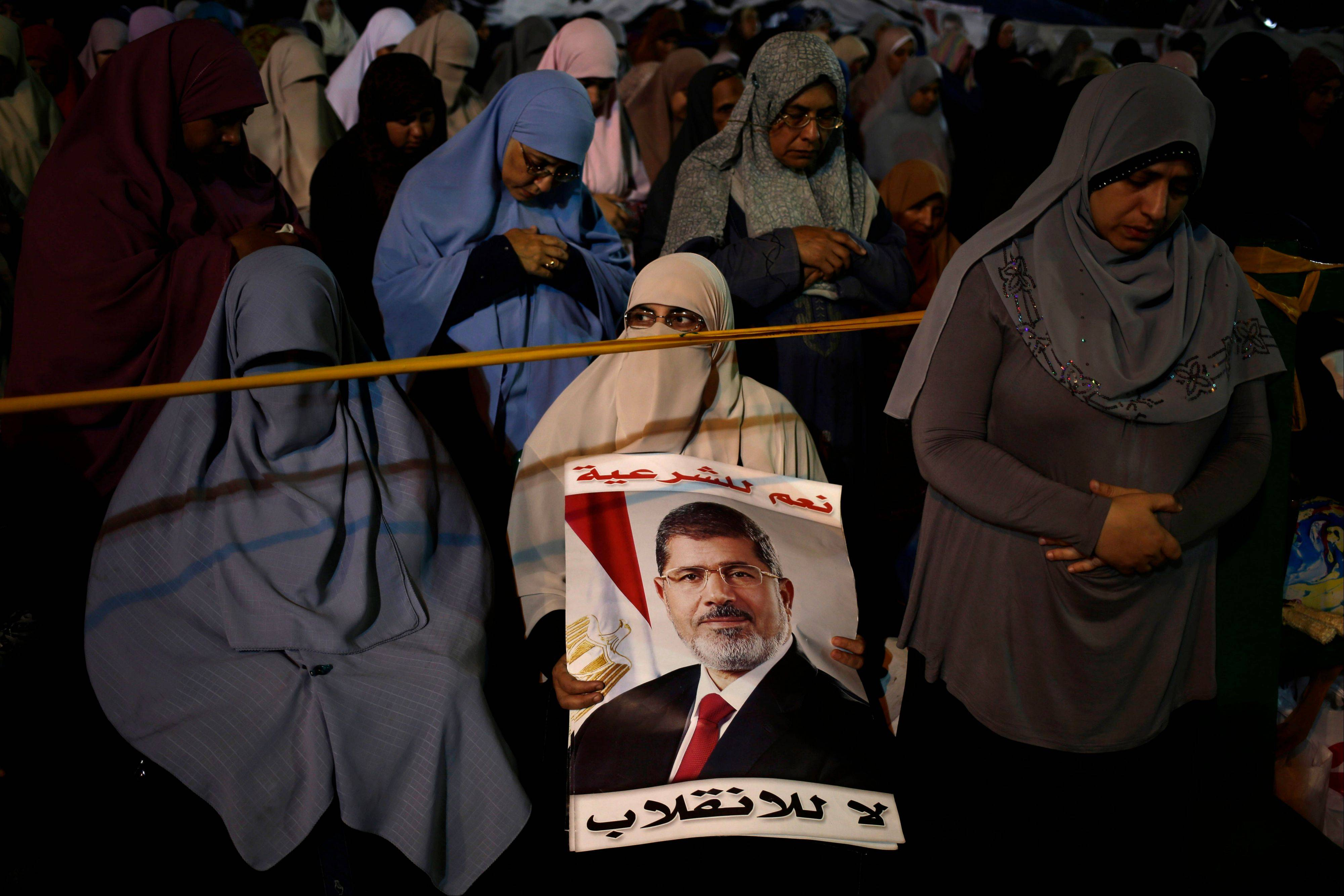 "Supporters of Egypt's ousted President Mohammed Morsi pray at Nasr City Sunday. Deadly clashes broke out during funerals of slain supporters of Egypt's ousted Islamist president Sunday, as the supreme leader of the Muslim Brotherhood urged his followers to stand fast after more than 80 of them were killed in weekend violence. The Arabic reads, ""Yes for the legitimacy, no for the coup."""