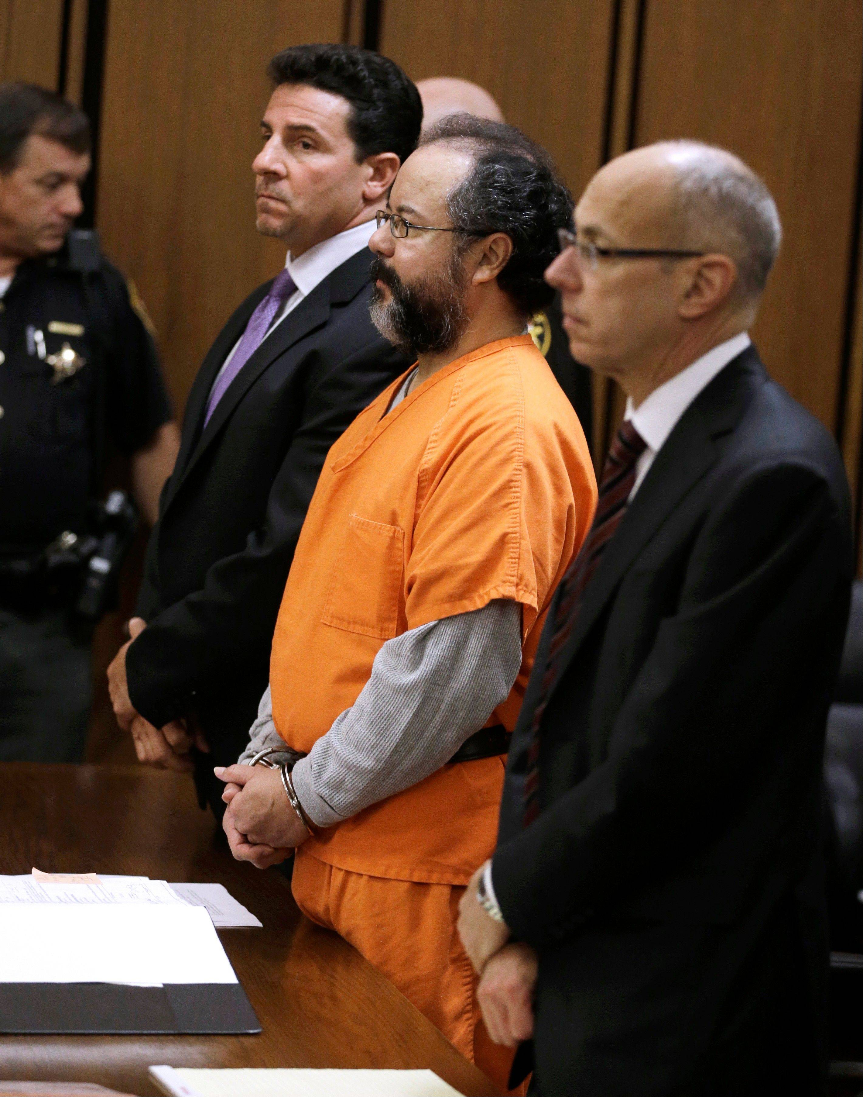 Ariel Castro, center, and defense attorneys Craig Weintraub, left, and Jaye Schlachet, stand in the courtroom Friday in Cleveland. Castro, who imprisoned three women in his home, pleaded guilty Friday to 937 counts in a deal to avoid the death penalty. In exchange, prosecutors recommended Castro be sentenced to life without parole plus 1,000 years.