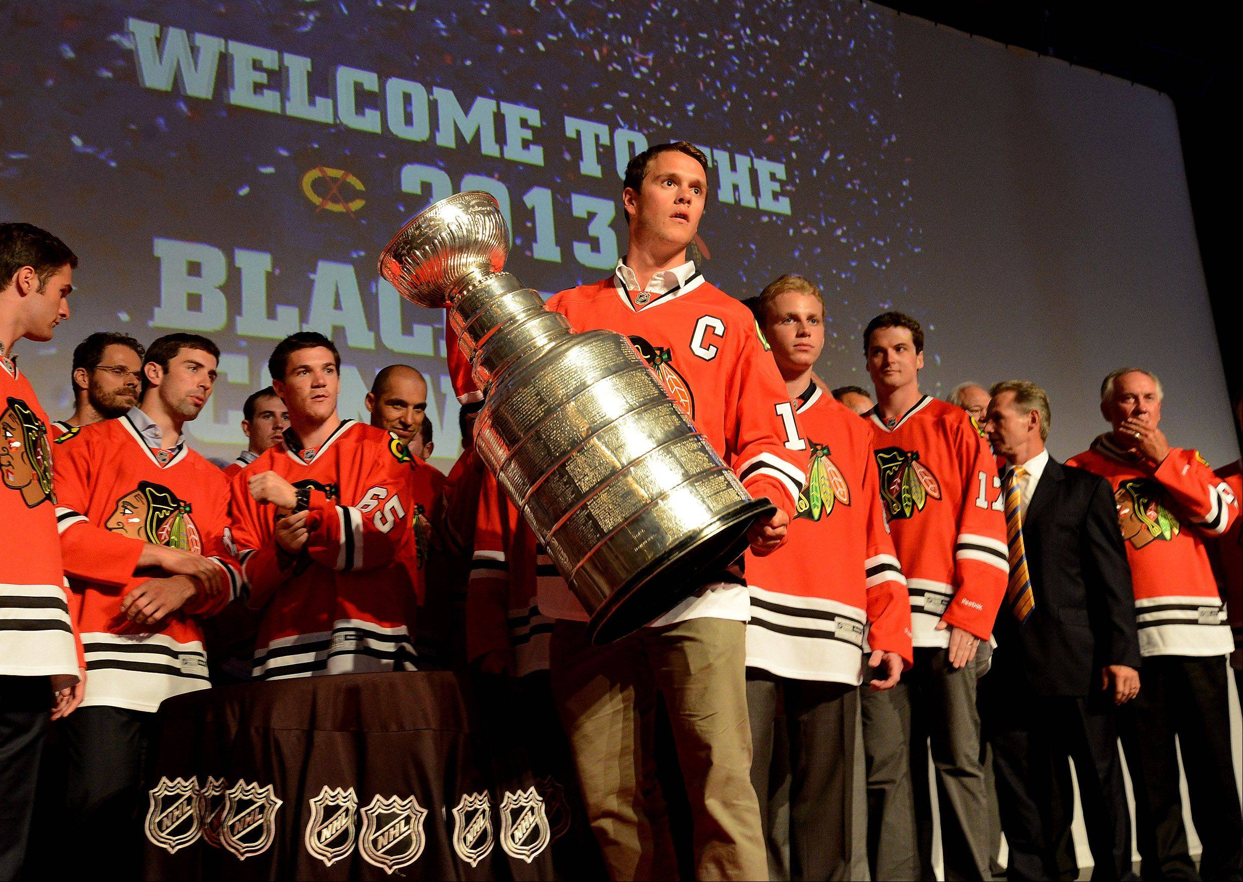 Captain Jonathan Toews prepares to hoist the Stanley Cup during opening night of the Sixth annual Blackhawks Convention.