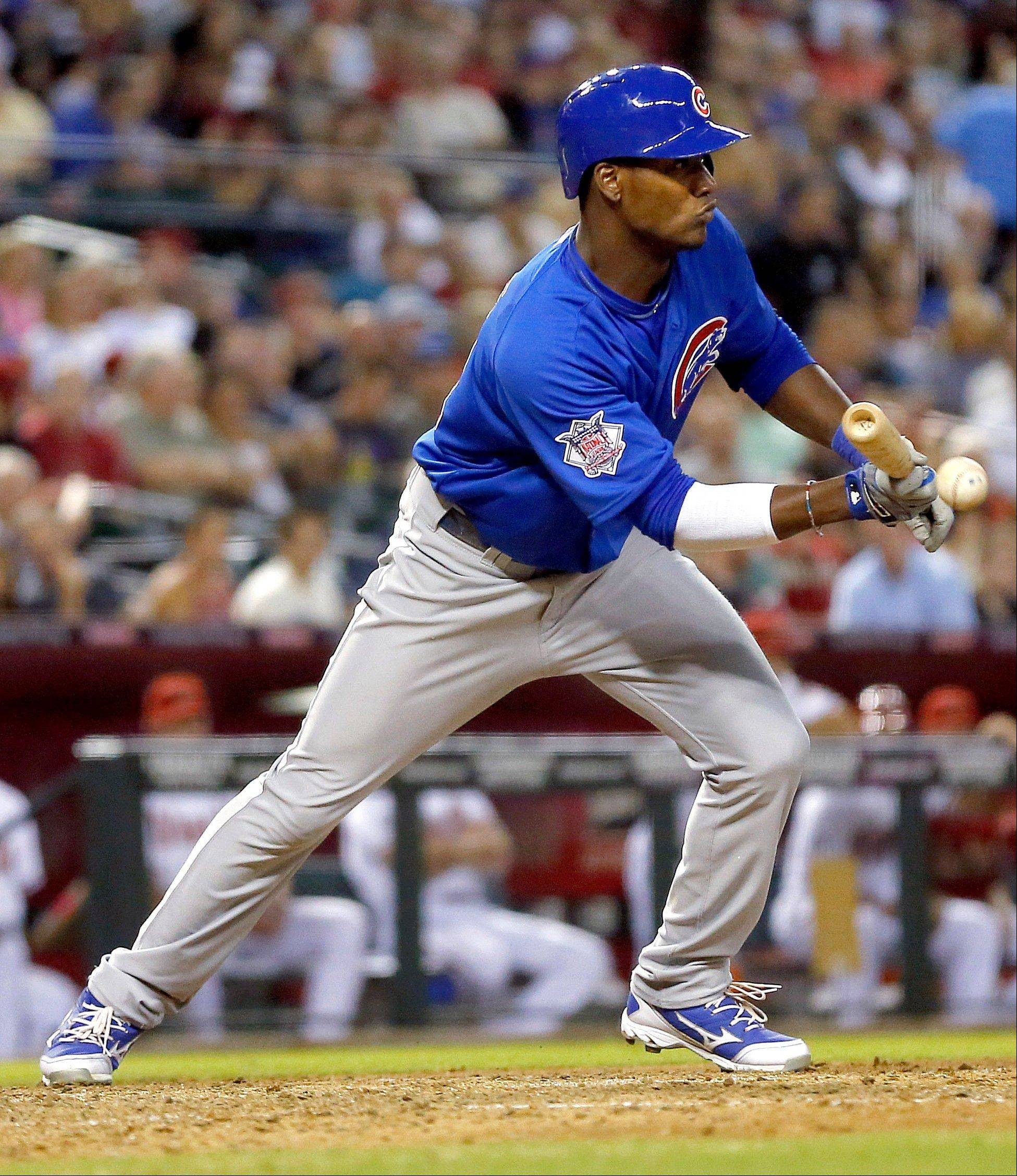 Junior Lake bunts for a base hit against the Arizona Diamondbacks during the sixth inning of a baseball game, Thursday, July 25, 2013, in Phoenix.