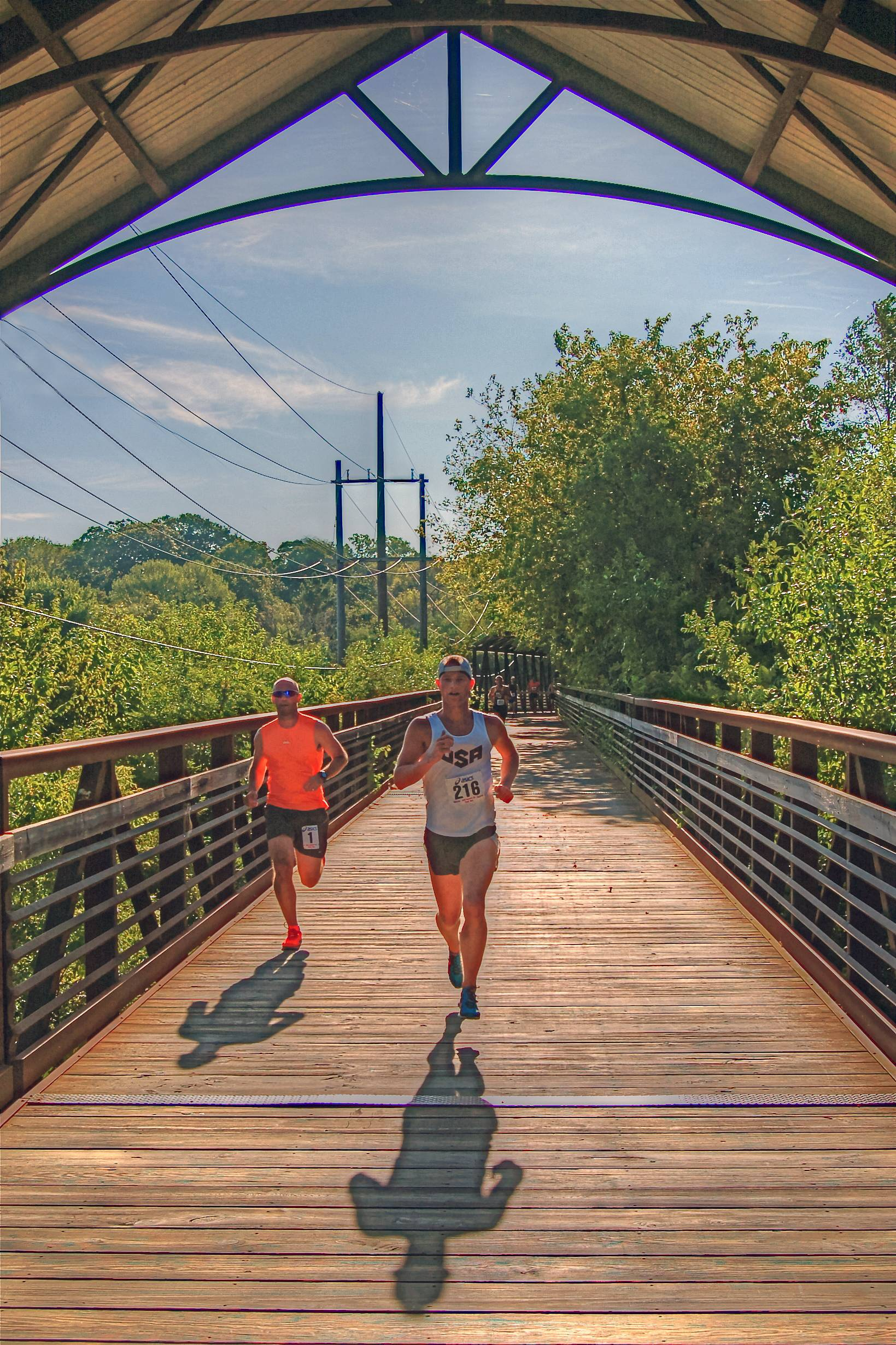 Runners of the Bob Leonard 5K run cross the Fox River bridge as they near the finish line in Pottawatomie Park, St. Charles.