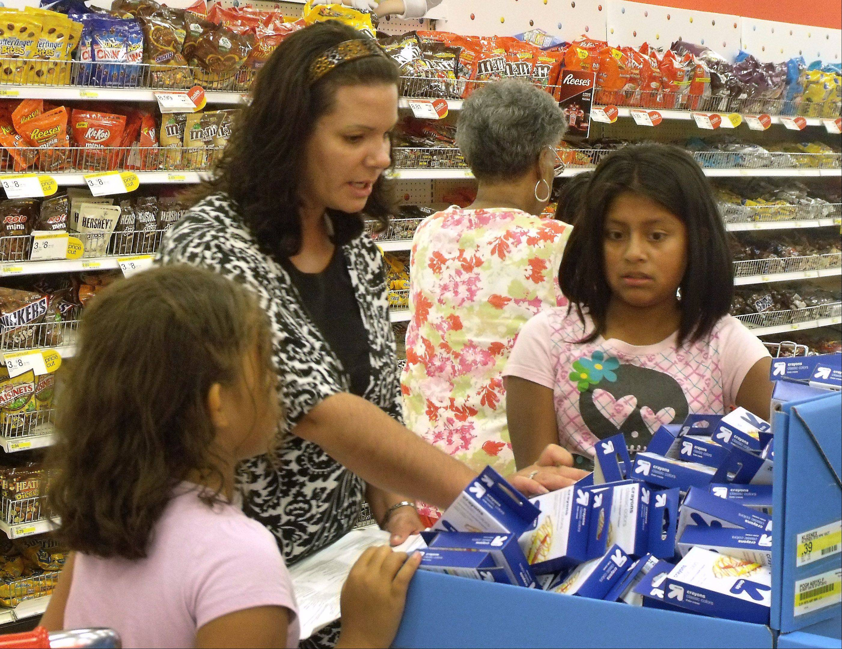 Salvation Army chaperon Jessica Ellingsworth helps Amanda Rinehart, 8, left, and Jazmin Farias, 9, decide which back-to-school supplies to buy Tuesday during a shopping spree at Target in Waukegan. Ten students received gift cards through a program to help needy children get ready for the classroom.