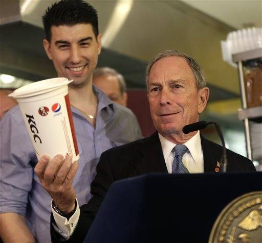 In this March 12, 2013 file photo, New York City Mayor Michael Bloomberg looks at a 64oz cup, as Lucky's Cafe owner Greg Anagnostopoulos, left, stands behind him. An appeals court ruled Tuesday, July 30, 2013 that New York City's Board of Health exceeded its legal authority and acted unconstitutionally when it tried to put a size limit on soft drinks served in city restaurants.