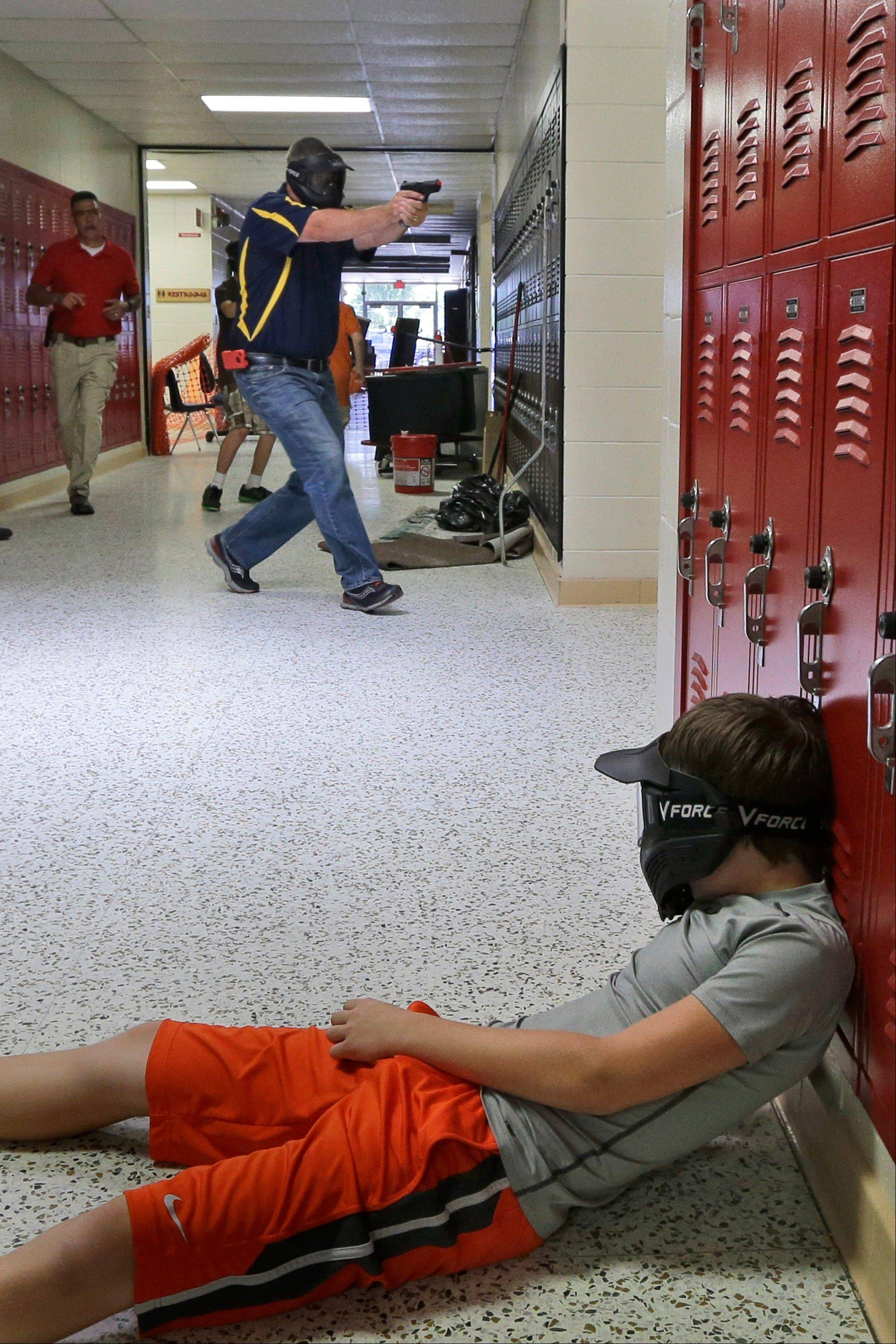 In this photo taken July 11, 2013, a Clarksville schools faculty member, wearing a protective mask, rear center, carries a practice handgun toward a classroom in the city�s high school in Clarksville, Ark., as students portray victims in a mock school shooting scenario. Twenty Clarksville School District staff members are training to be armed security guards on campus.