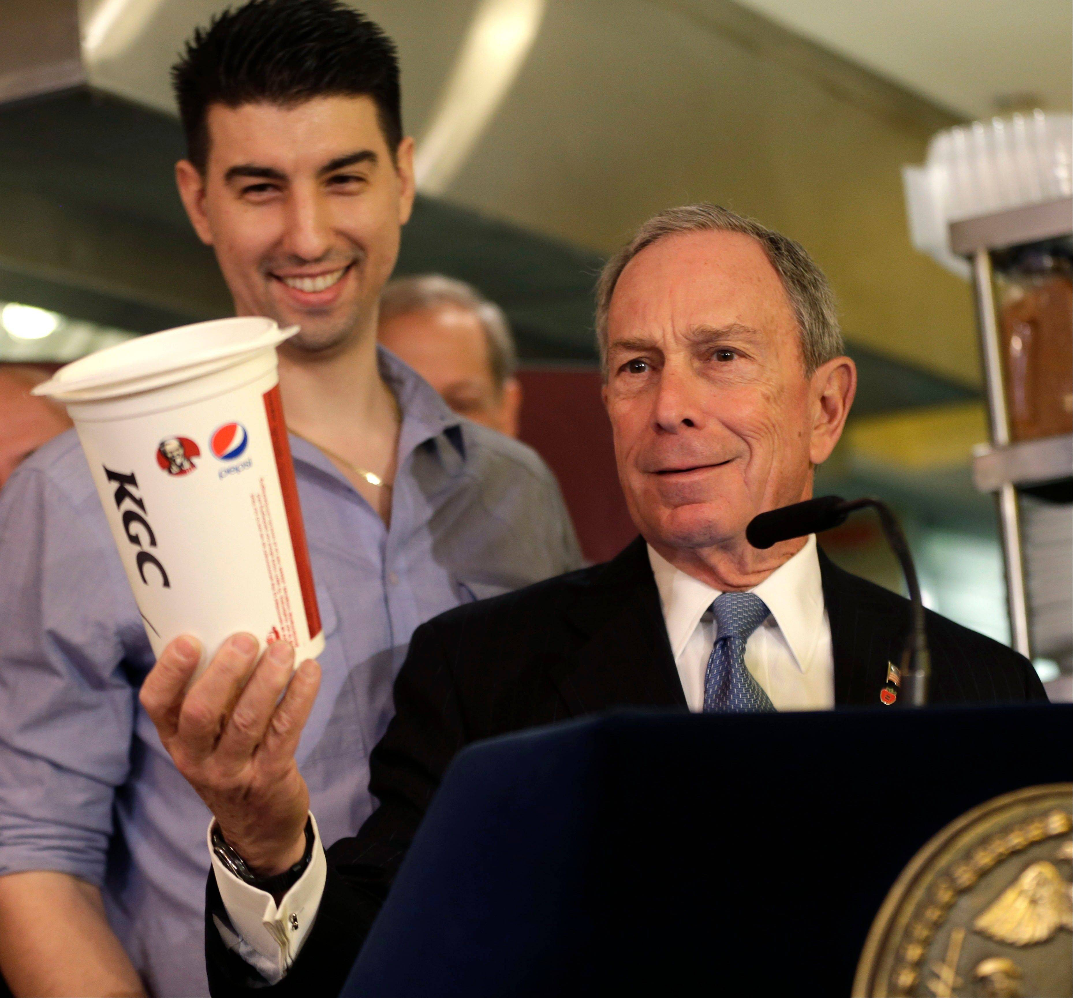New York City Mayor Michael Bloomberg looks at a 64-ounce cup, as Lucky's Cafe owner Greg Anagnostopoulos, left, stands behind him. An appeals court ruled Tuesday that New York City's Board of Health exceeded its legal authority and acted unconstitutionally when it tried to put a size limit on soft drinks served in city restaurants.