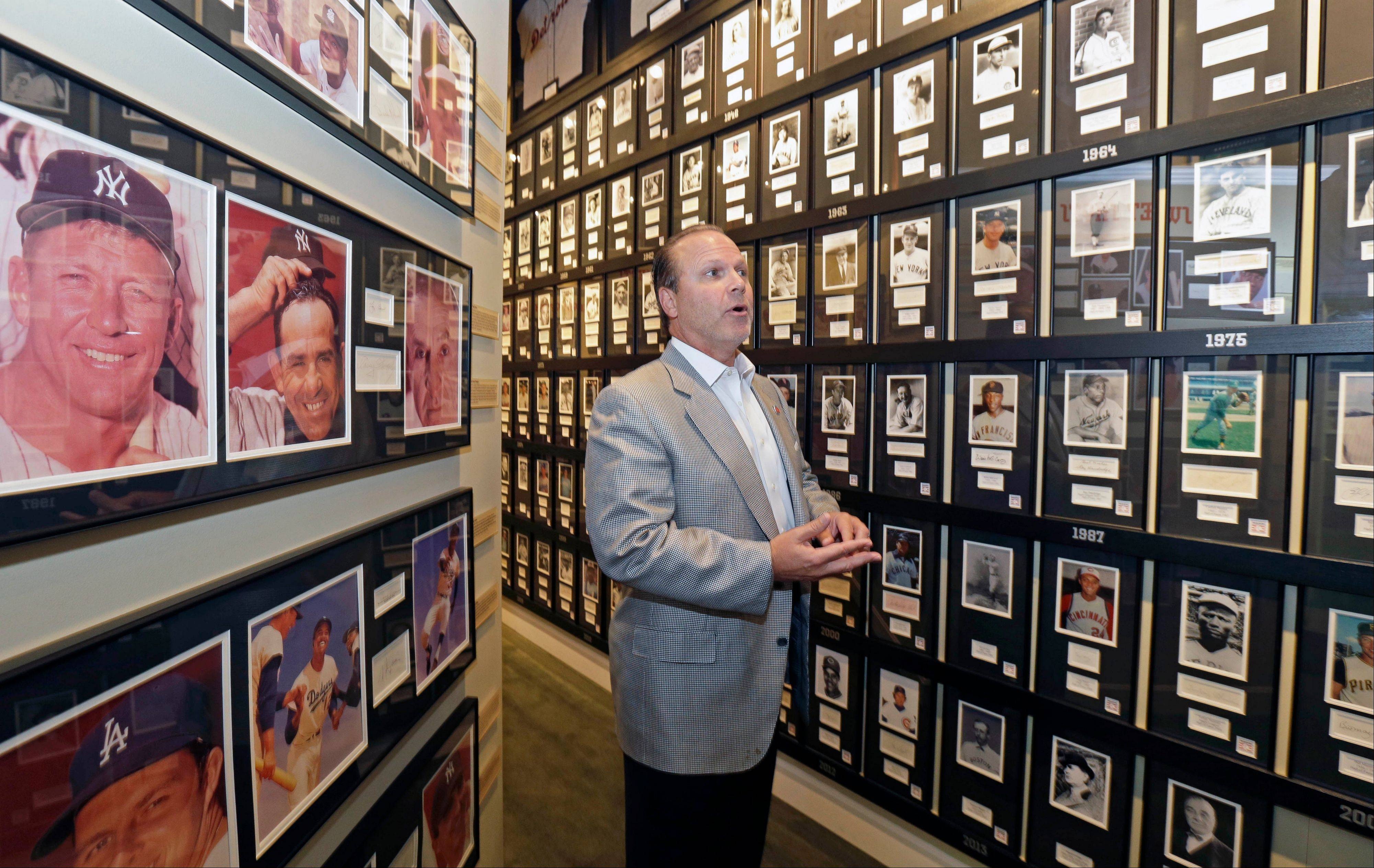 Owner Bob Crotty stands next to a wall featuring photos and autographs of all the members of baseball's Hall of Fame inside the Green Diamond Gallery in Cincinnati.