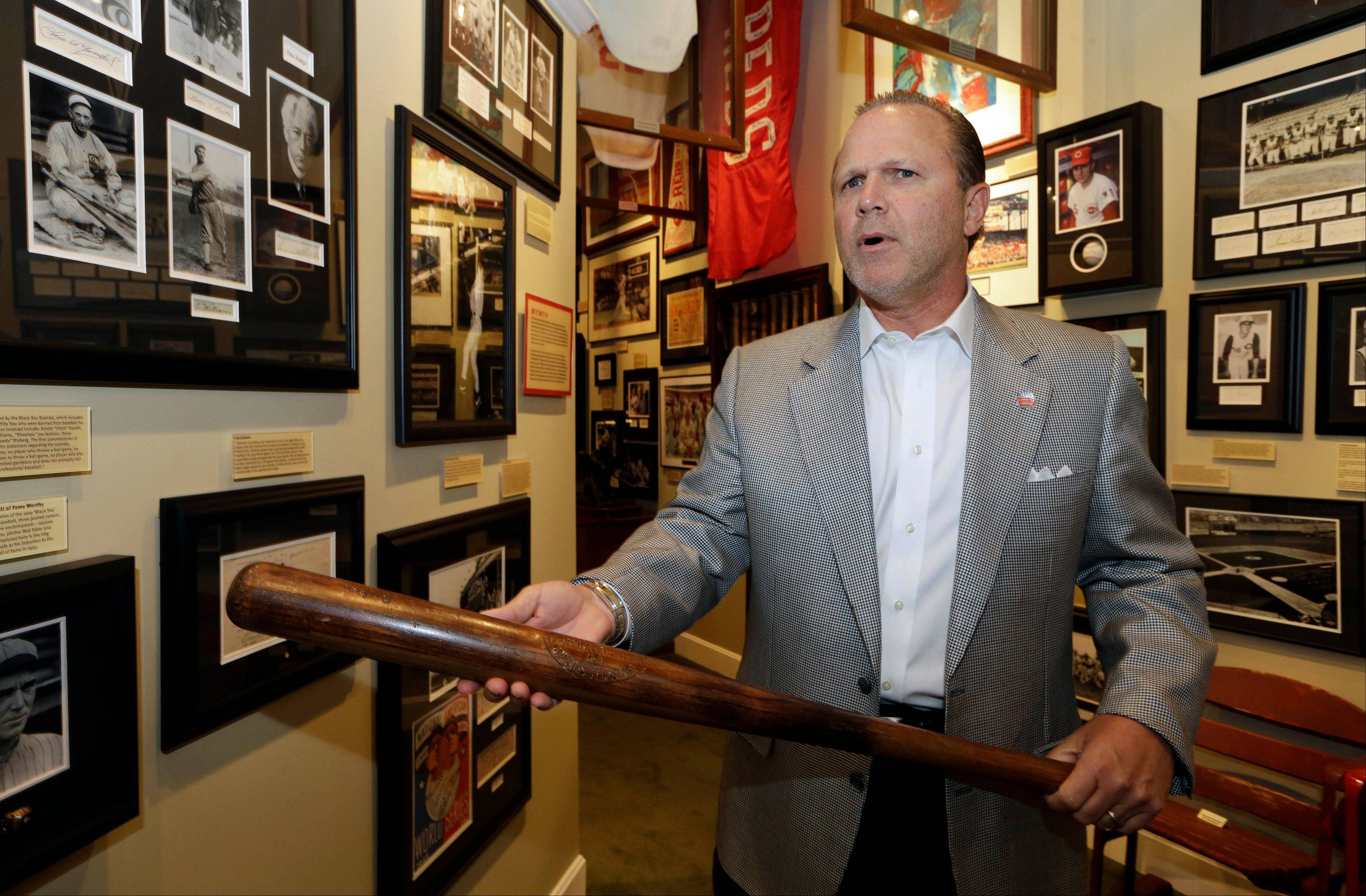 Owner Bob Crotty holds a bat used by Shoeless Joe Jackson as he stands next to a display on the 1919 Chicago White Sox scandal inside the Green Diamond Gallery in Cincinnati.