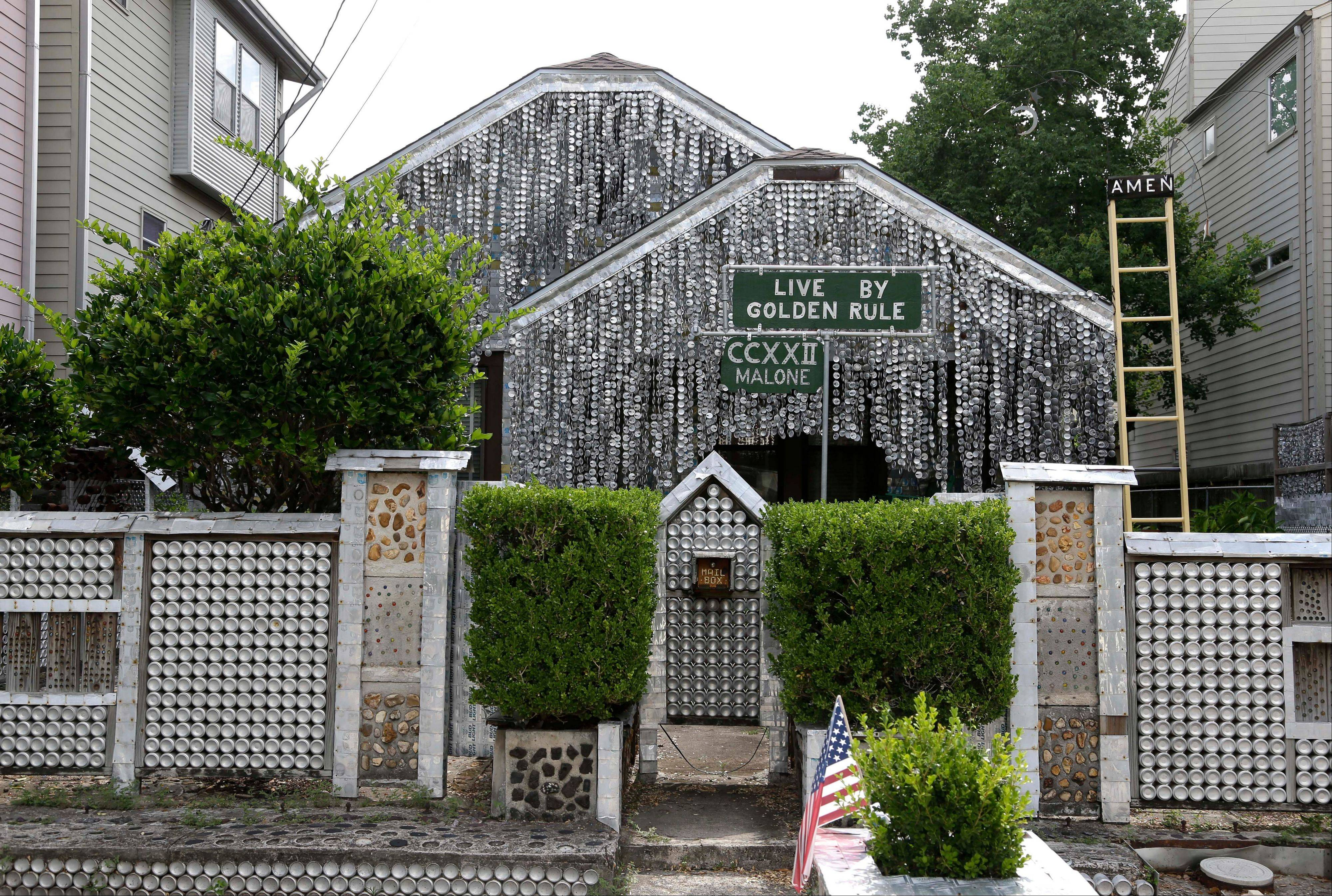 The beer can house, a Houston landmark, sits between newer homes. Former owner John Milkovisch covered the outside on the house with siding made of cut and flatten beer cans and garlands made from the lids.