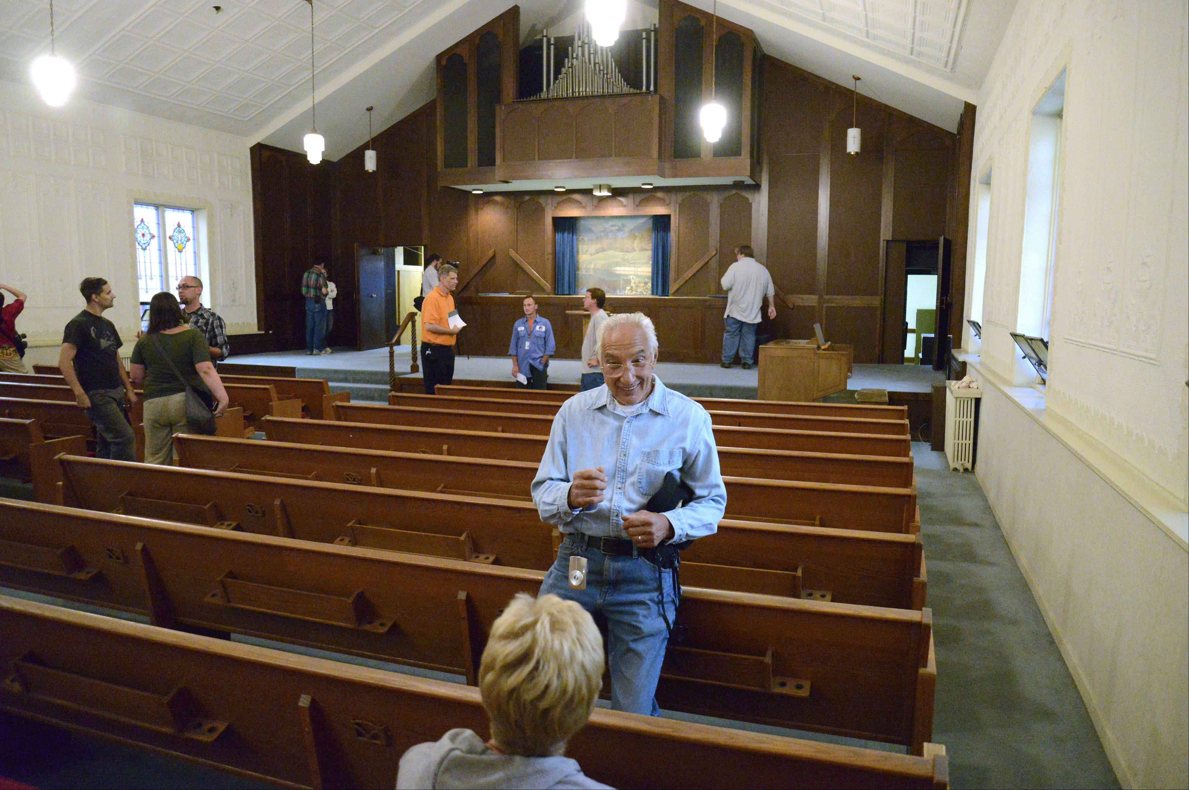Art de la Cruz shares his memories of growing up in the First Baptist Church congregation to friend Sandy Eckblade on a tour of the building Tuesday. The city owns the building and is considering whether to tear some or all of it down or do some repairs while awaiting a buyer.