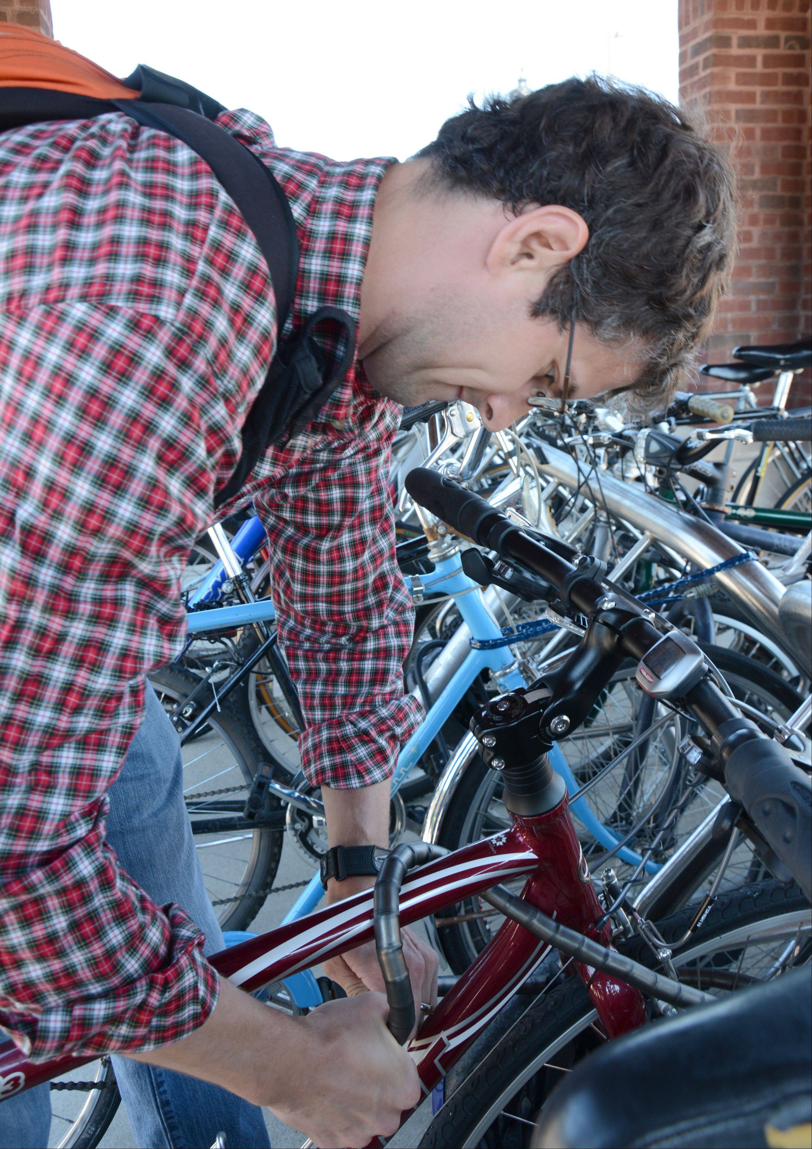 Mike Walsh, of Arlington Heights, locks up his bike at the Arlington Heights train station. Walsh had a bike stolen years ago, but hopes his bike lock is enough of a deterrent to prevent it from happening again.