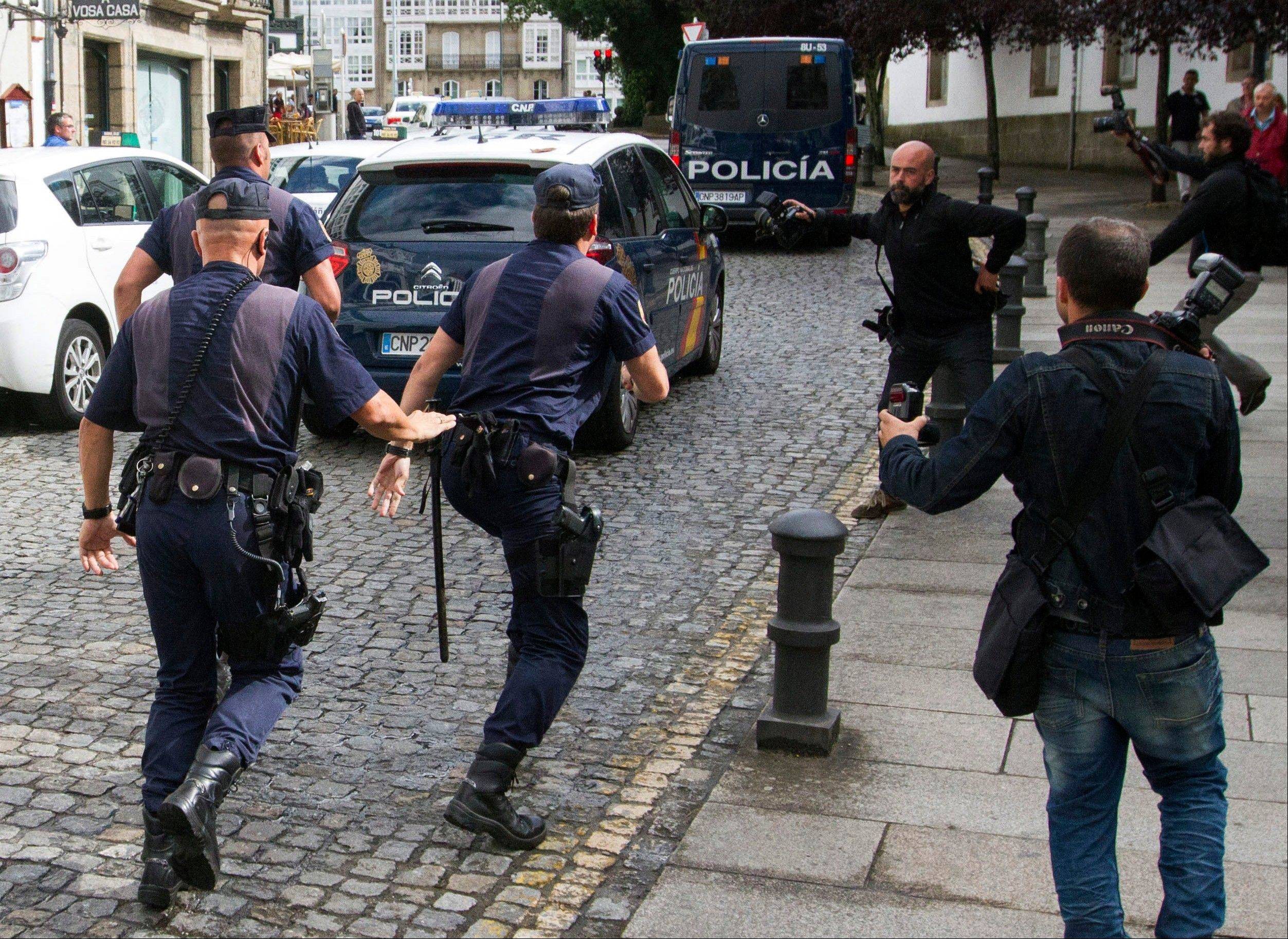 Media run after a police car carrying arrested train driver Francisco Jose Garzon Amo, unseen, to testify in court in Santiago de Compostela, Spain, Sunday. Amo was provisionally charged Tuesday with multiple counts of negligent homicide.