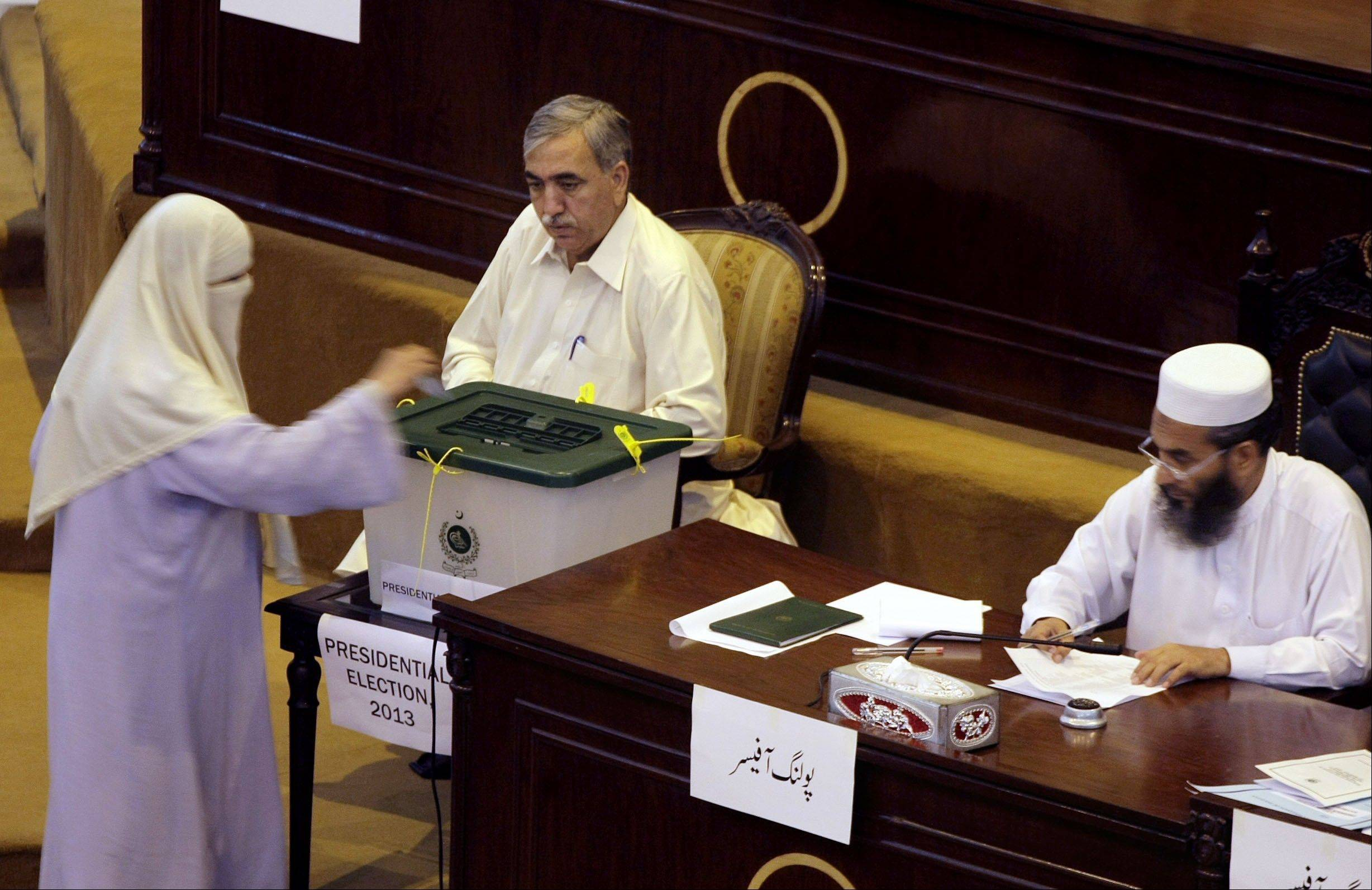 A Pakistani lawmaker casts her vote for the presidential election at the Provincial assembly in Peshawar, Pakistan, Tuesday, July 30, 2013. Pakistani lawmakers elected Mamnoon Hussain, a textile businessman, as the country's next president.
