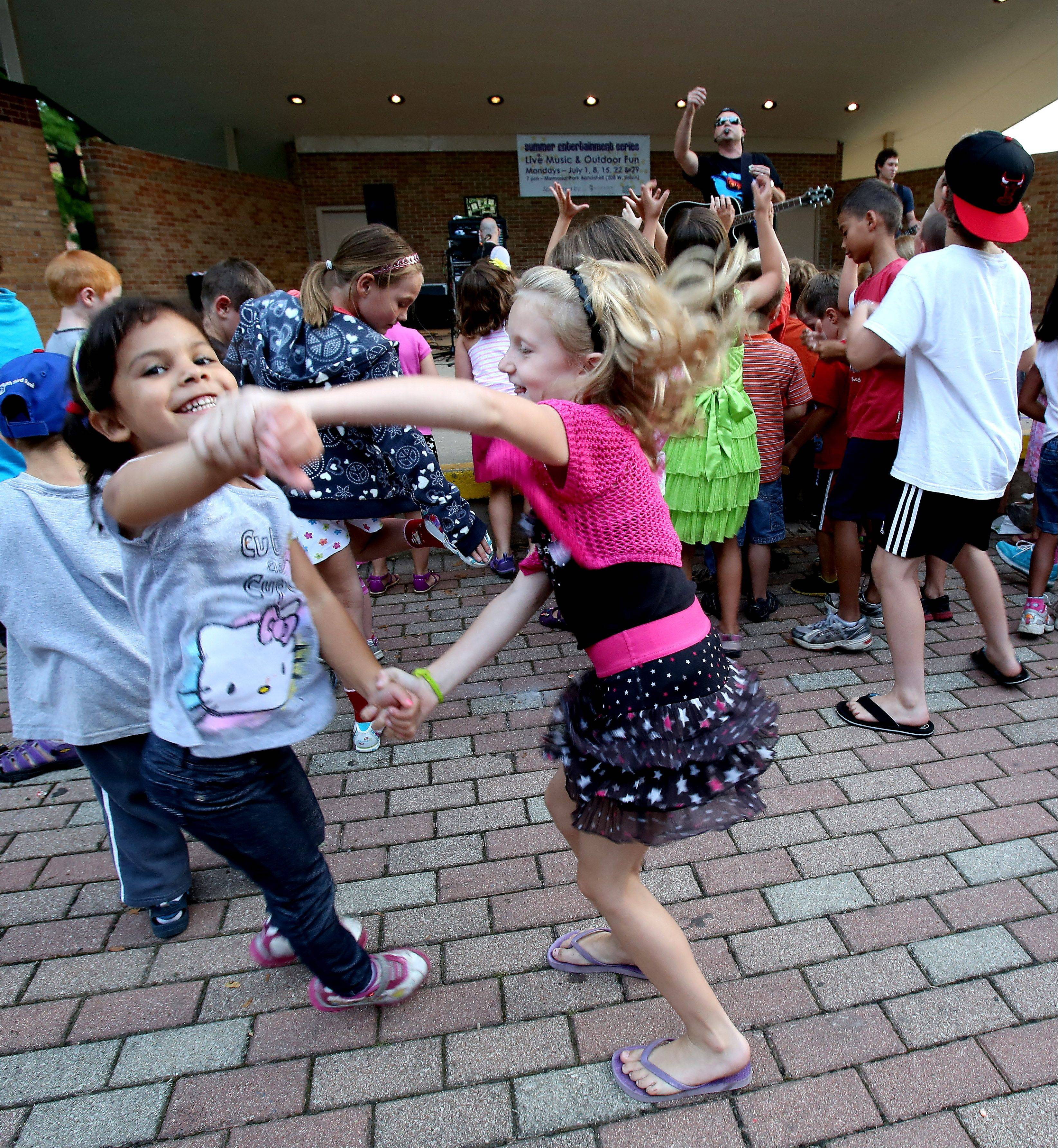 Andria Montgomery, 5, left of Lombard and Hayden Yates, 6, right, of Wheaton dance during a Radio Rock concert in Memorial Park in Wheaton yesterday. The show was part of the Wheaton Park District's Summer Entertainment Series.