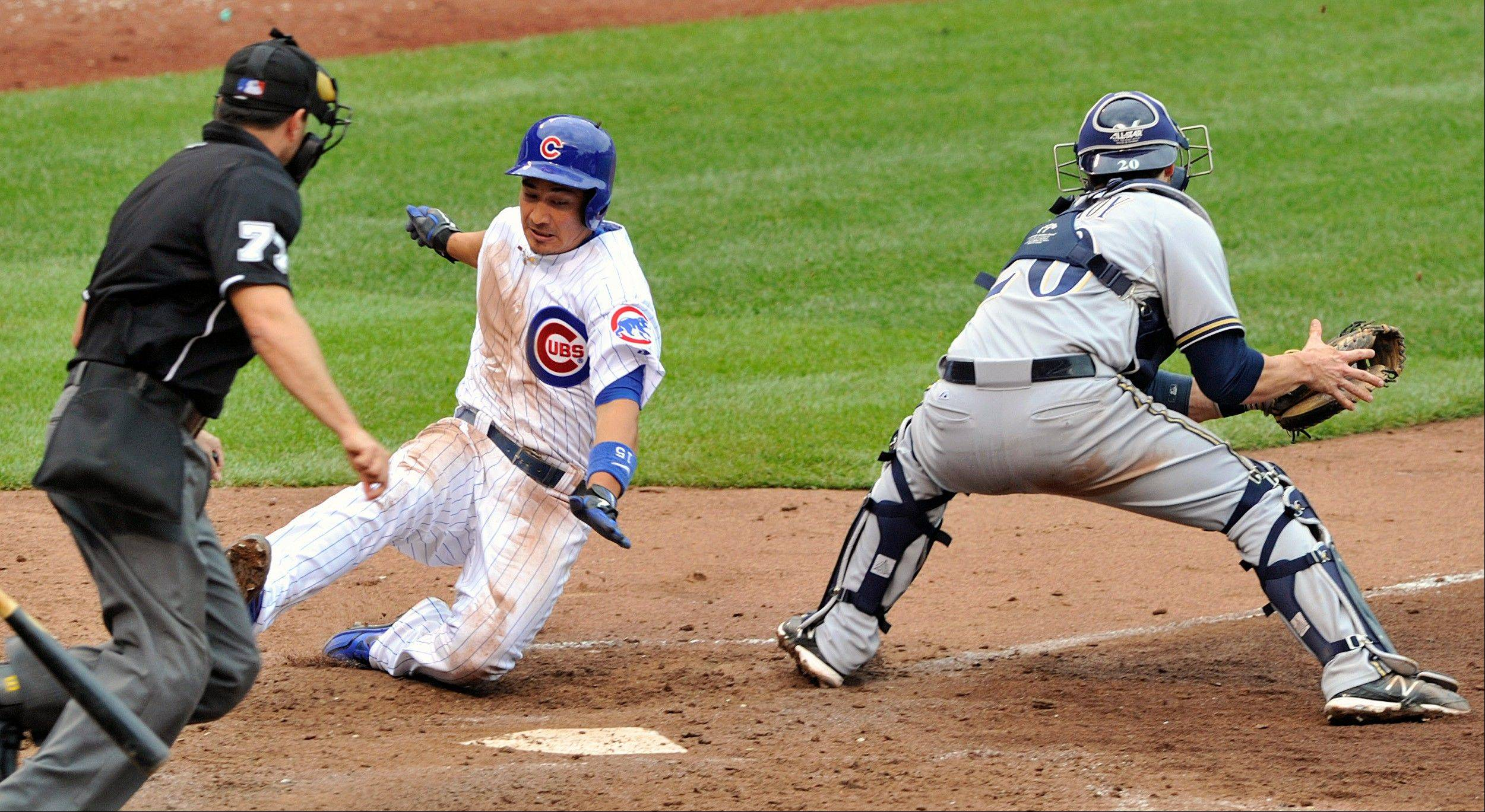 Chicago Cubs' Darwin Barney left, avoids the tag of Milwaukee Brewers catcher Jonathan Lucroy to score on an RBI single by Carlos Villanueva during the fifth inning of a baseball game Tuesday in Chicago.