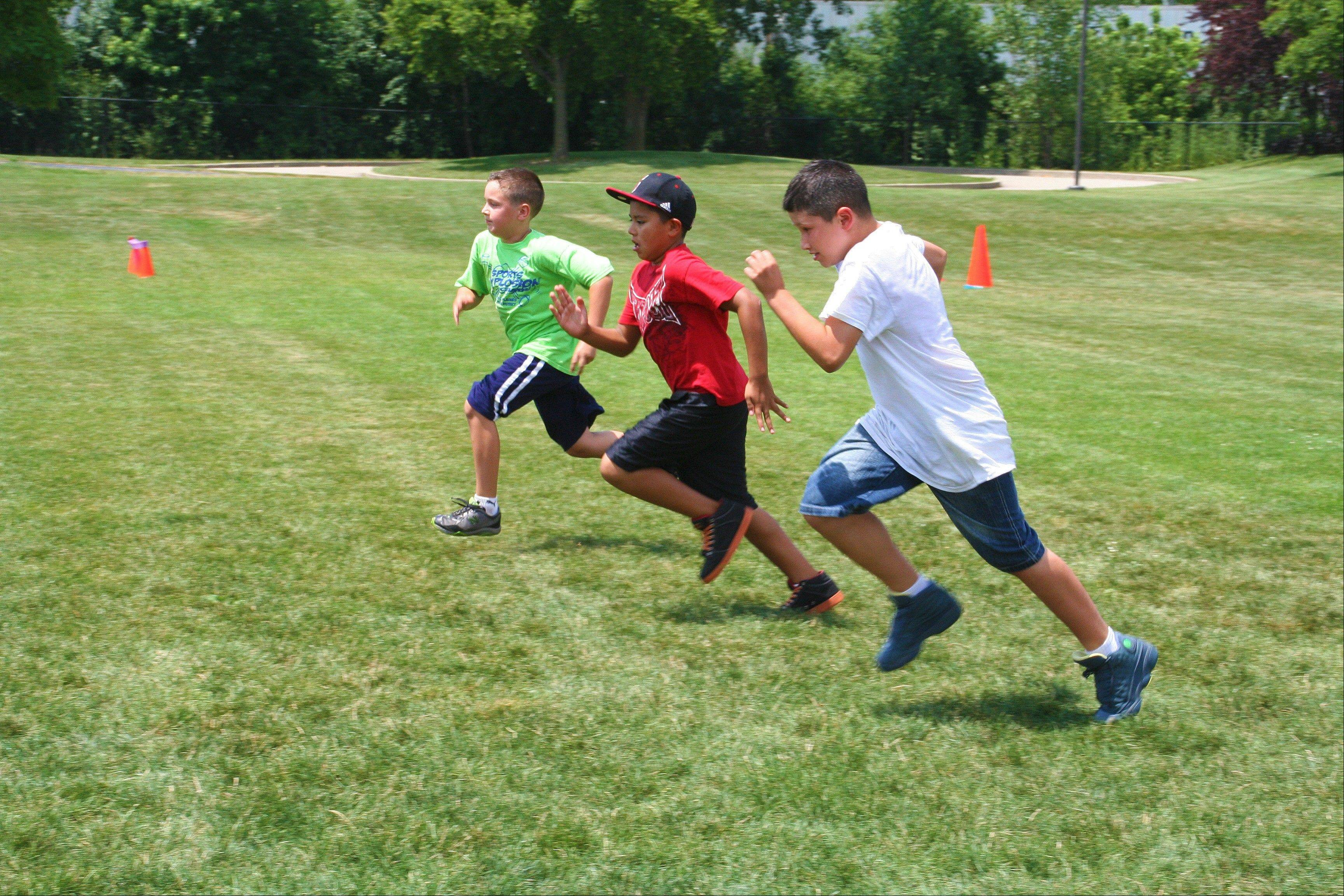 Campers from Sports Xplosion (green), West Park (red) and Camp Opeka (white) take to the field in the 50-yard dash during the 2013 All Camp Field Day at Prairie Lakes July 17.