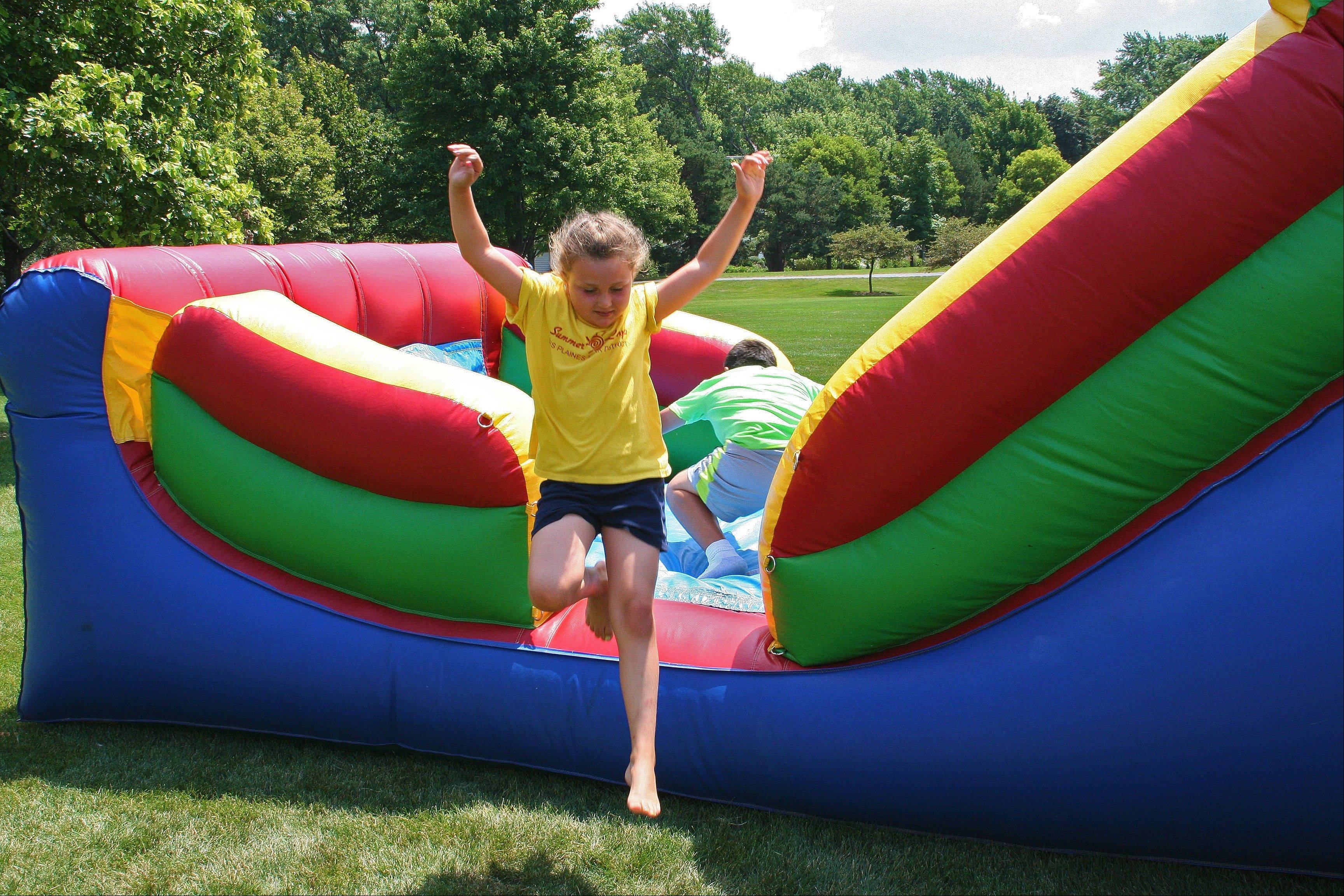 Camp Chickagami beats the Sports Xplosion camp in a race through the inflatable obstacle course during the 2013 All Camp Field Day at Prairie Lakes July 17.