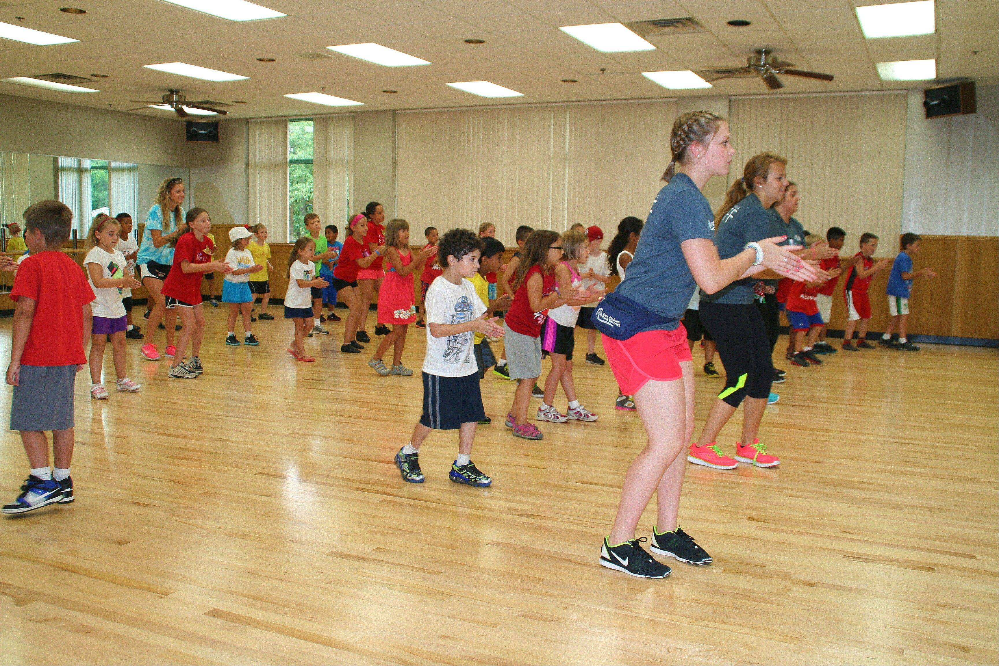 Dance and Arts Camp counselor, Kim Diebold, teach day campers the Tonto during the 2013 All Camp Field Day at Prairie Lakes July 17.