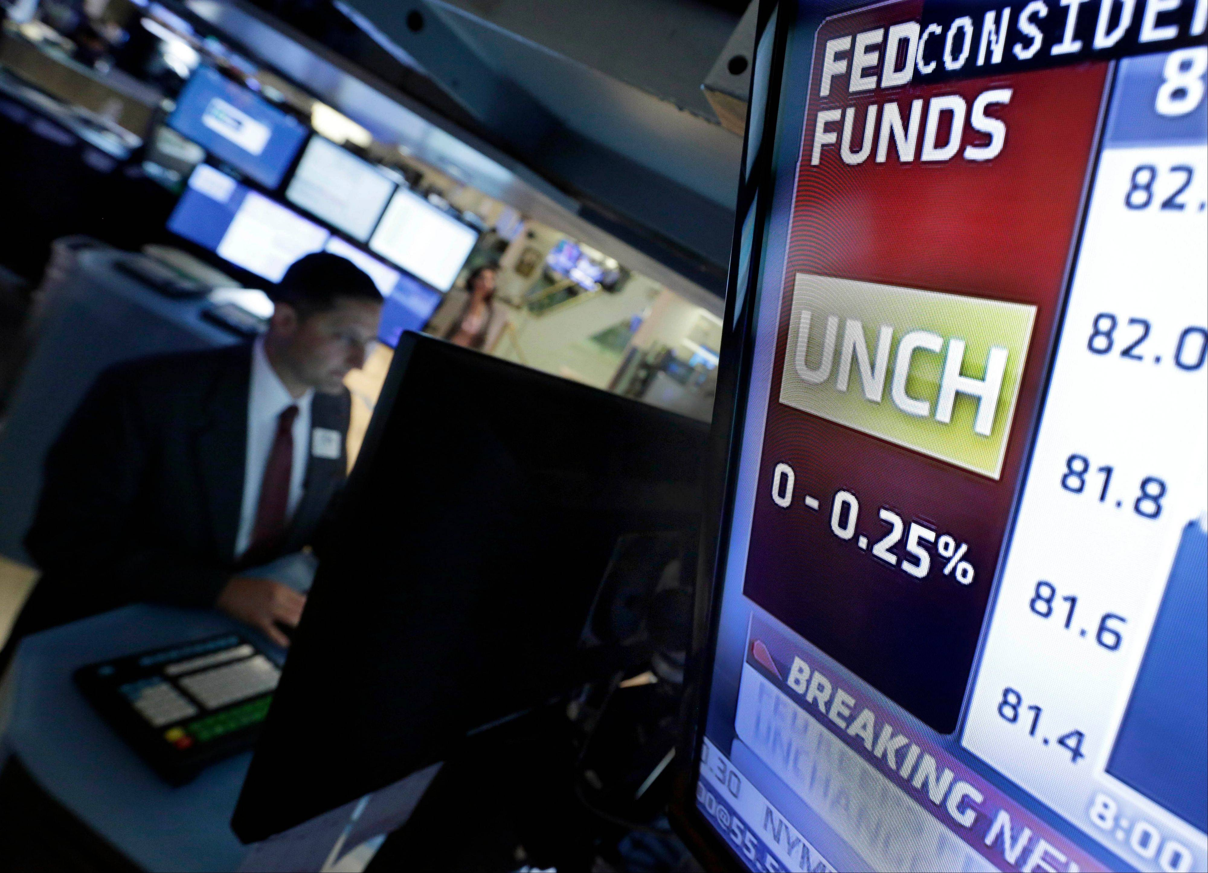 A television screen on the floor of the New York Stock Exchange shows the rate decision by the Federal Reserve Wednesday. The Federal Reserve says the U.S. economy is growing modestly, a downgrade from its June assessment.