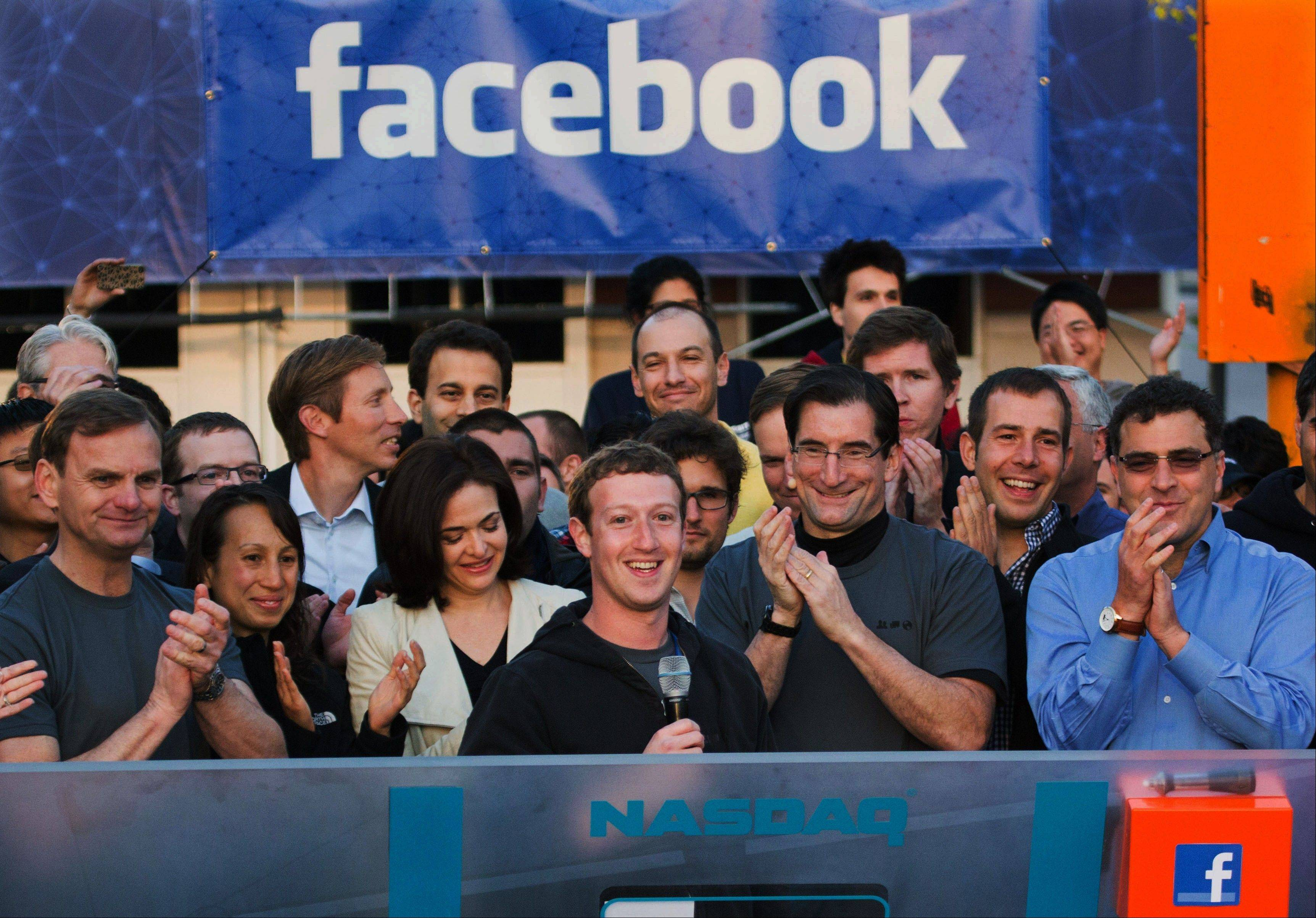In this May 18, 2012, file photo, Facebook founder, Chairman and CEO Mark Zuckerberg, center, rings the Nasdaq opening bell from Facebook headquarters in Menlo Park, Calif. Facebook's stock finally passed its IPO price of $38 before the market opened Wednesday.