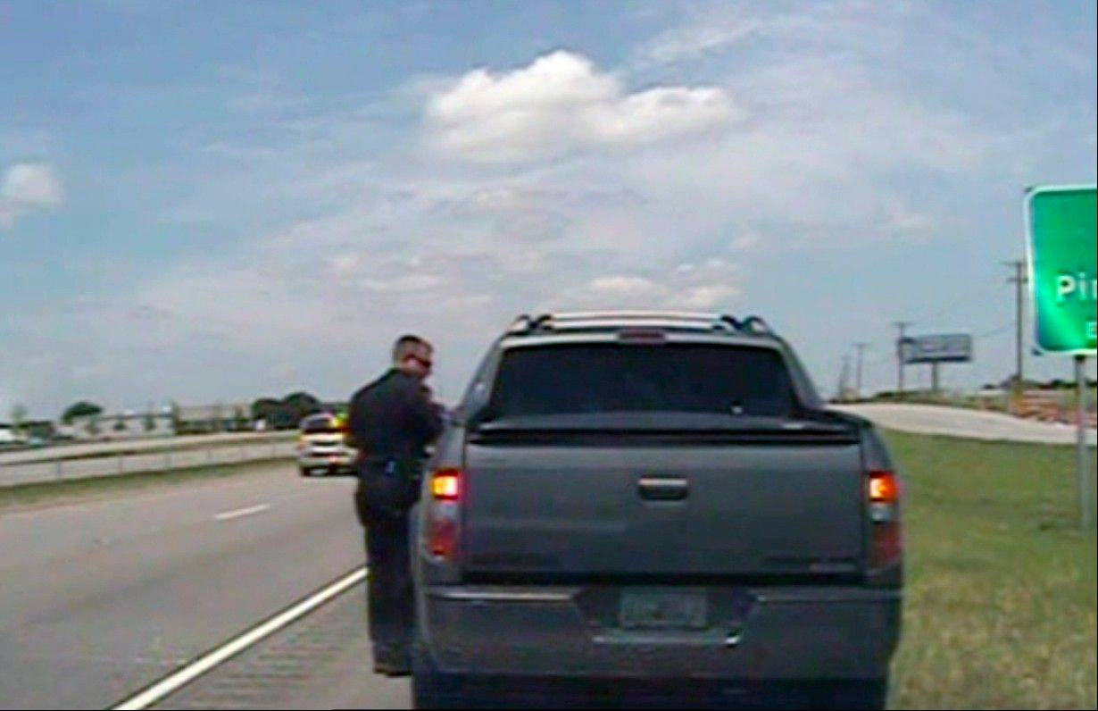 In this image taken from dashcam video provided by the City of Forney Police Department, a police officer speaks with George Zimmerman, the neighborhood watch volunteer acquitted by a Florida jury of charges in the fatal shooting of a black teenager, after he was pulled over for speeding near Dallas on Sunday, July 28, 2013.