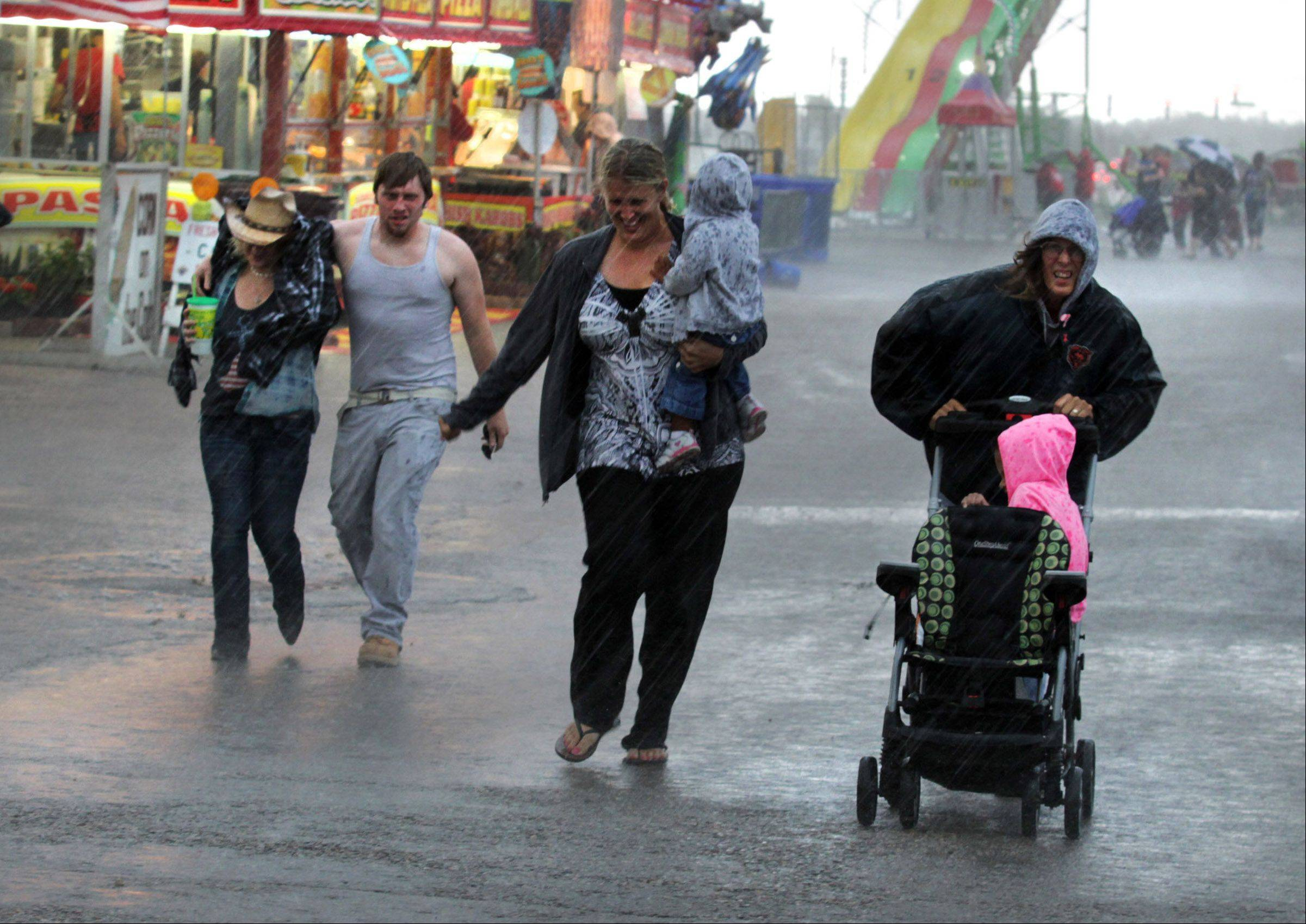 Visitors run for cover as heavy rain falls on July 26 at the Lake County Fair in Grayslake. The antique tractor parade, Midwest Truck and Tractor Pull, Battle of the Barns, and main stage bands were canceled due to weather.